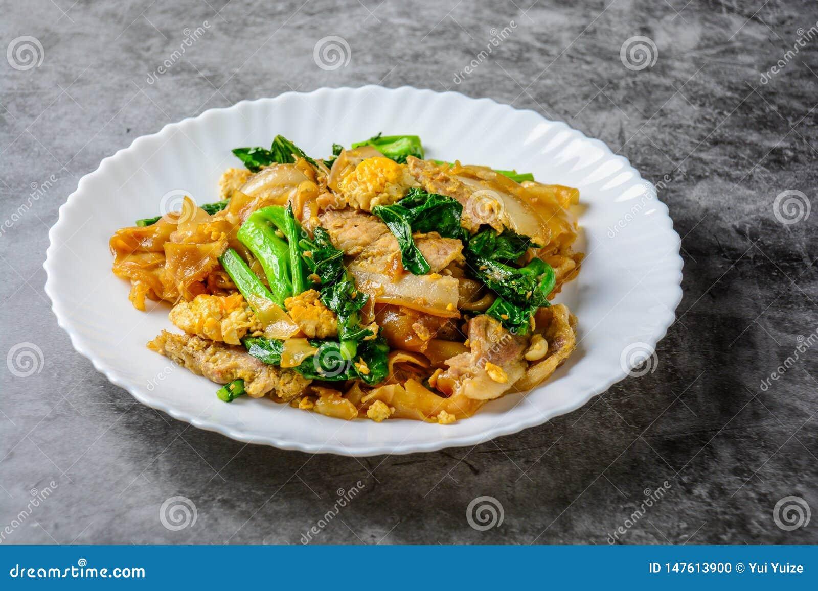 混乱油煎的新鲜的米线用切的猪肉、鸡蛋和无头甘蓝