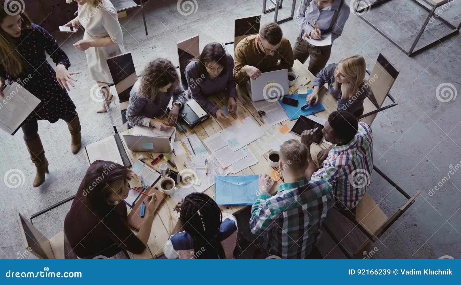 混合的族种坐在桌上的企业队顶视图在顶楼办公室和工作 妇女经理带来本文