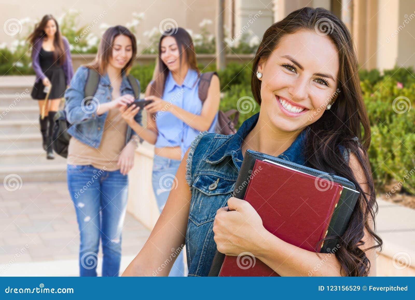 混合的族种有教科书的女孩学生在校园里