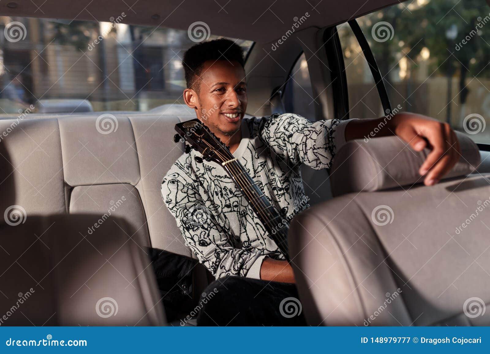 混合的族种的一个愉快的人,在汽车进来,拿着一把吉他,充满心情,户内汽车的图象