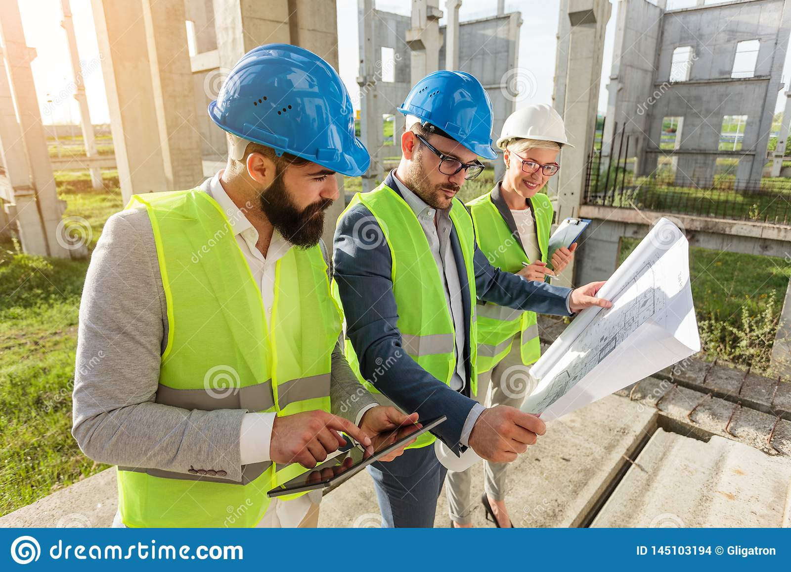 混合群年轻建筑师和土木工程师或者见面在一大工地工作的商务伙伴