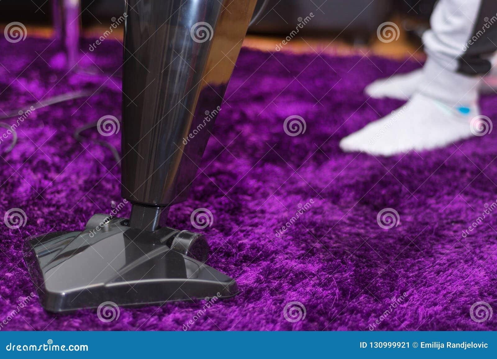 清洗紫色地毯的妇女与现代吸尘器在客厅