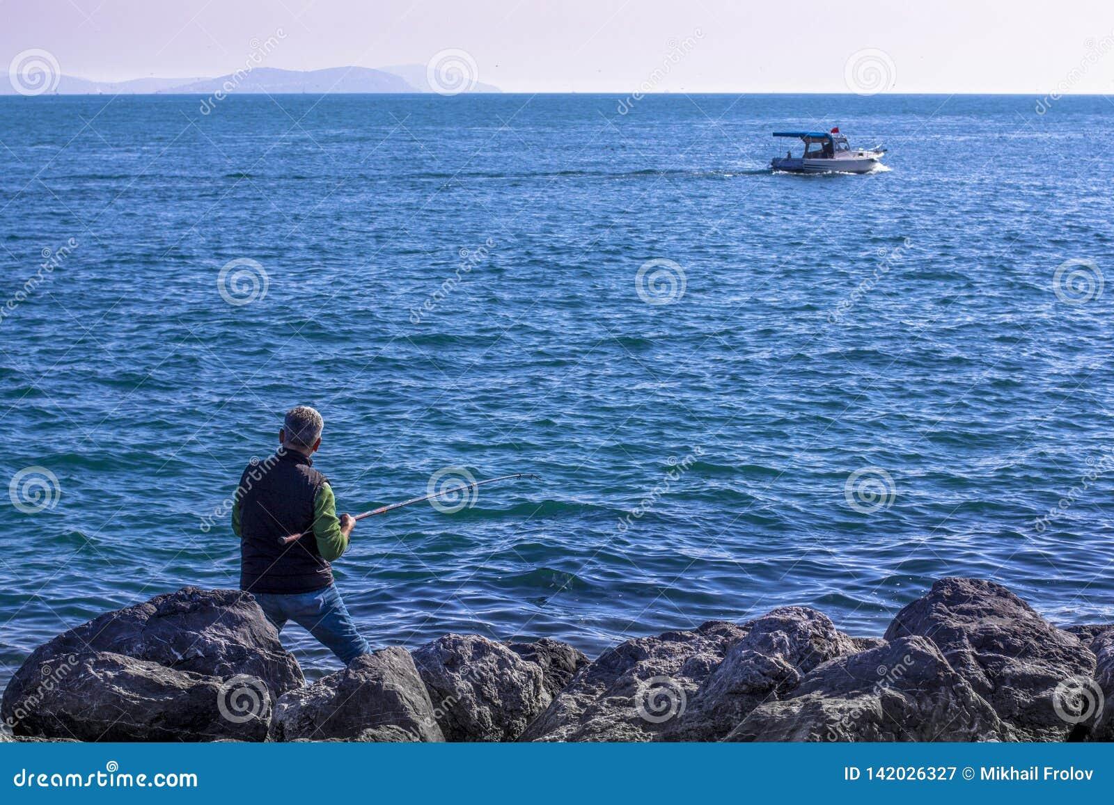 渔夫和小船在海 堤防在伊斯坦布尔