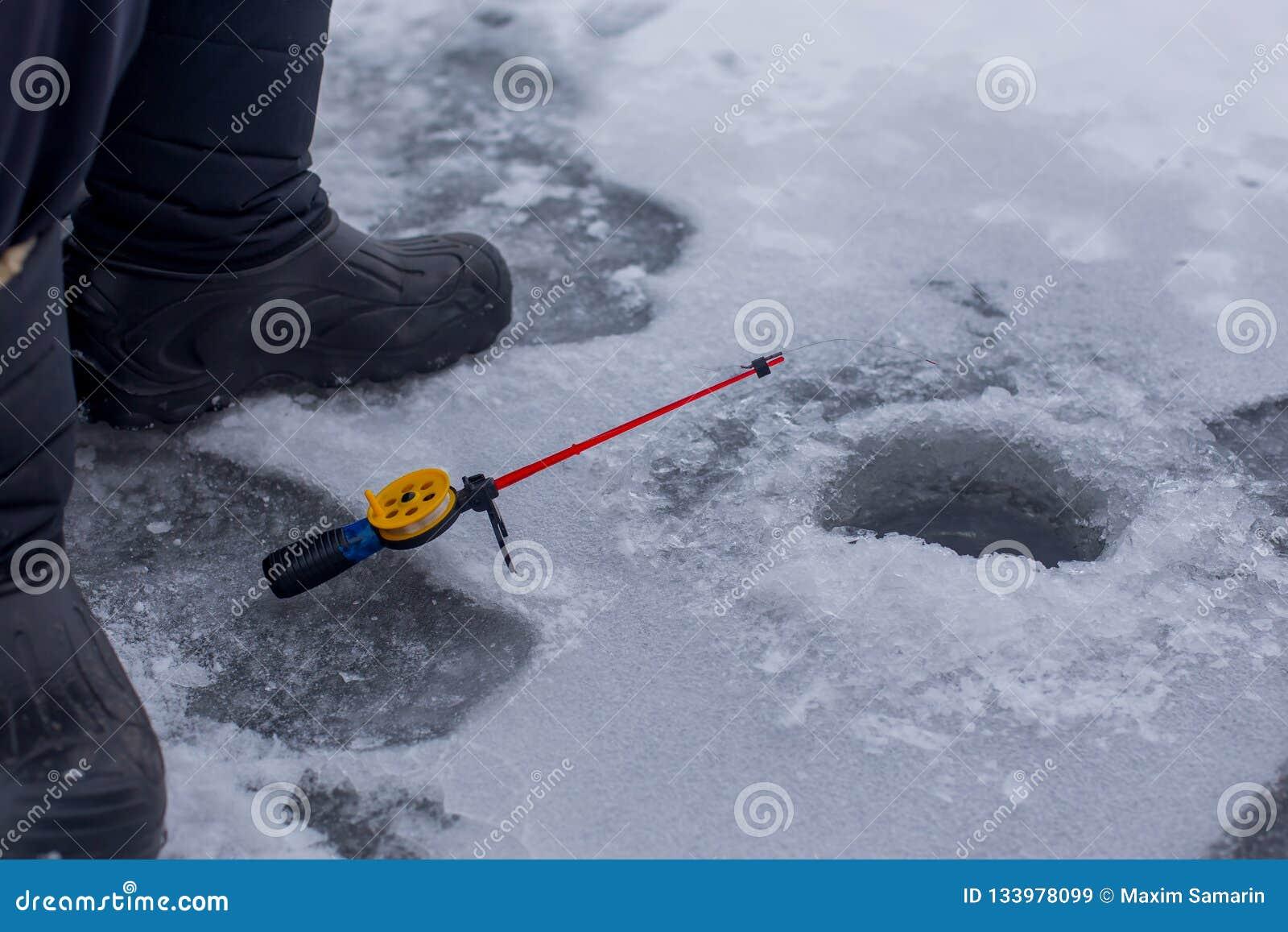 渔夫在冬天钓鱼竿的抓住鱼的特写镜头手在有孔的冻河