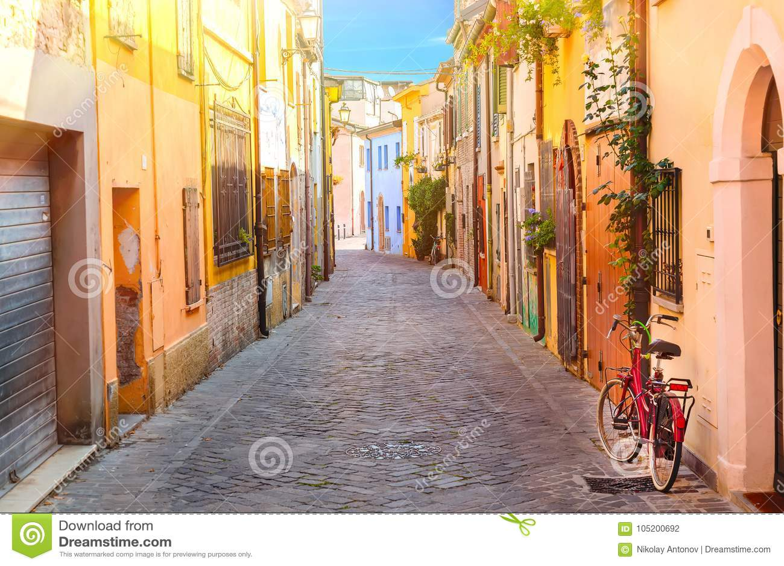 渔夫有五颜六色的房子的圣Guiliano和自行车村庄的狭窄的街道在清早在里米尼,意大利