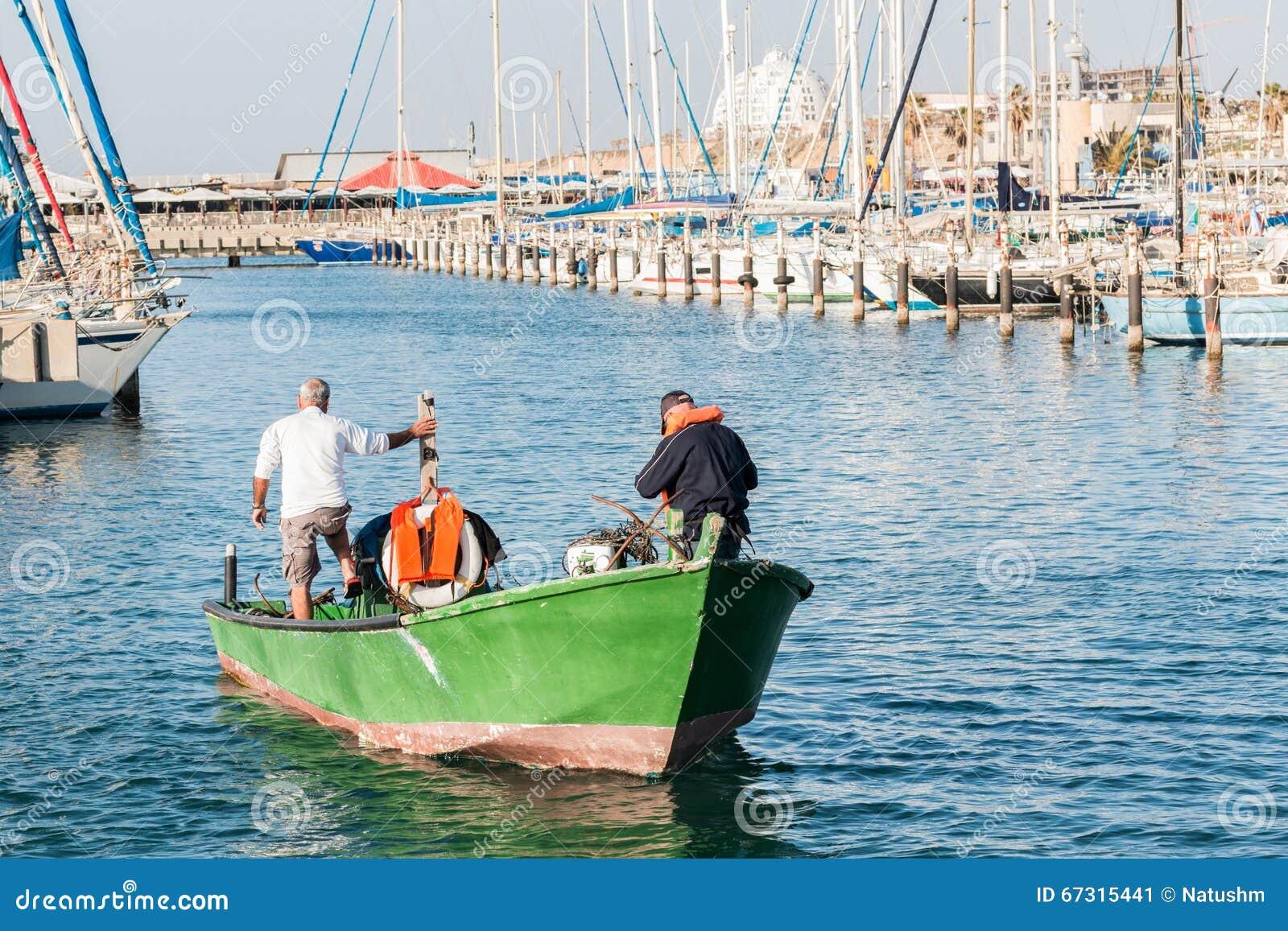 渔夫,有一条绿色小船的,在海滩在亚实基伦,以色列