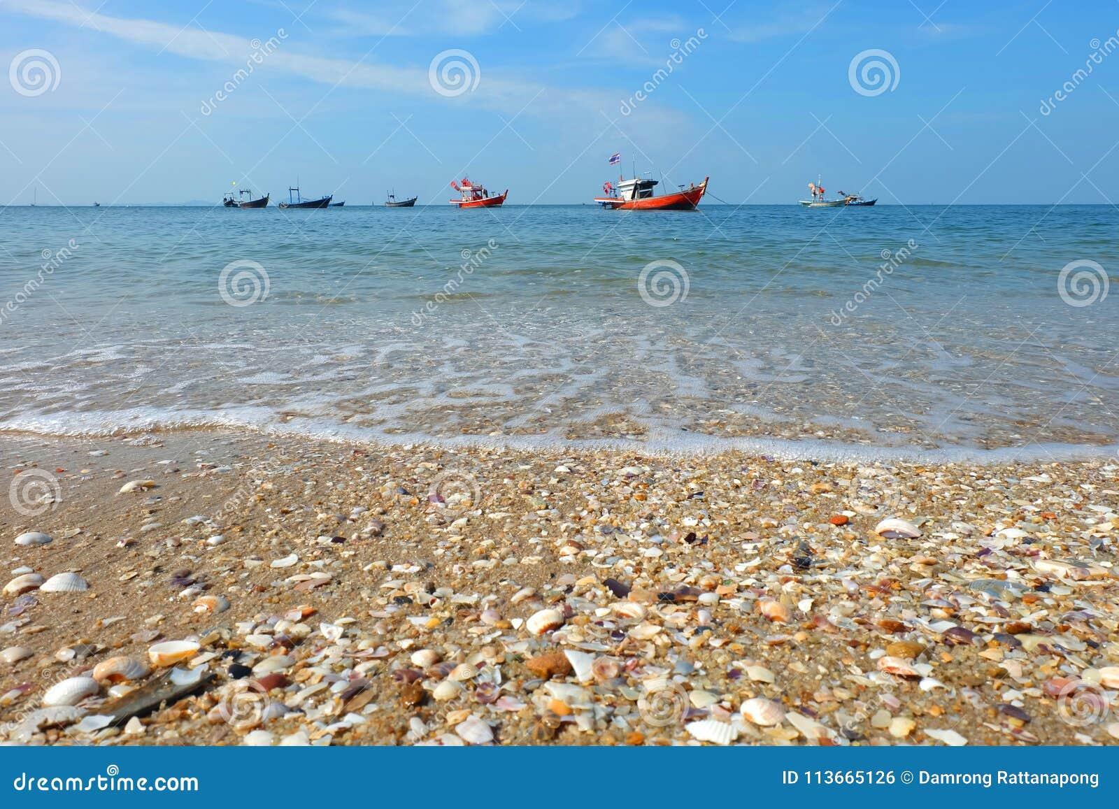 渔船说谎在船锚由海和海滩和五颜六色的壳