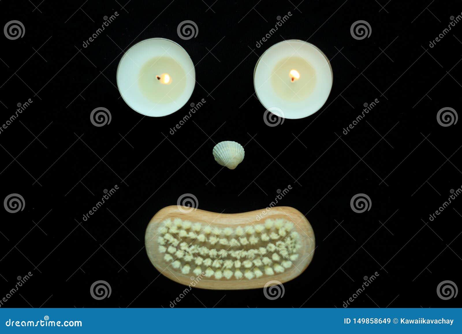 温泉健康概念、面孔与眼睛蜡烛,贝壳鼻子和一把木身体刷子的嘴在黑背景