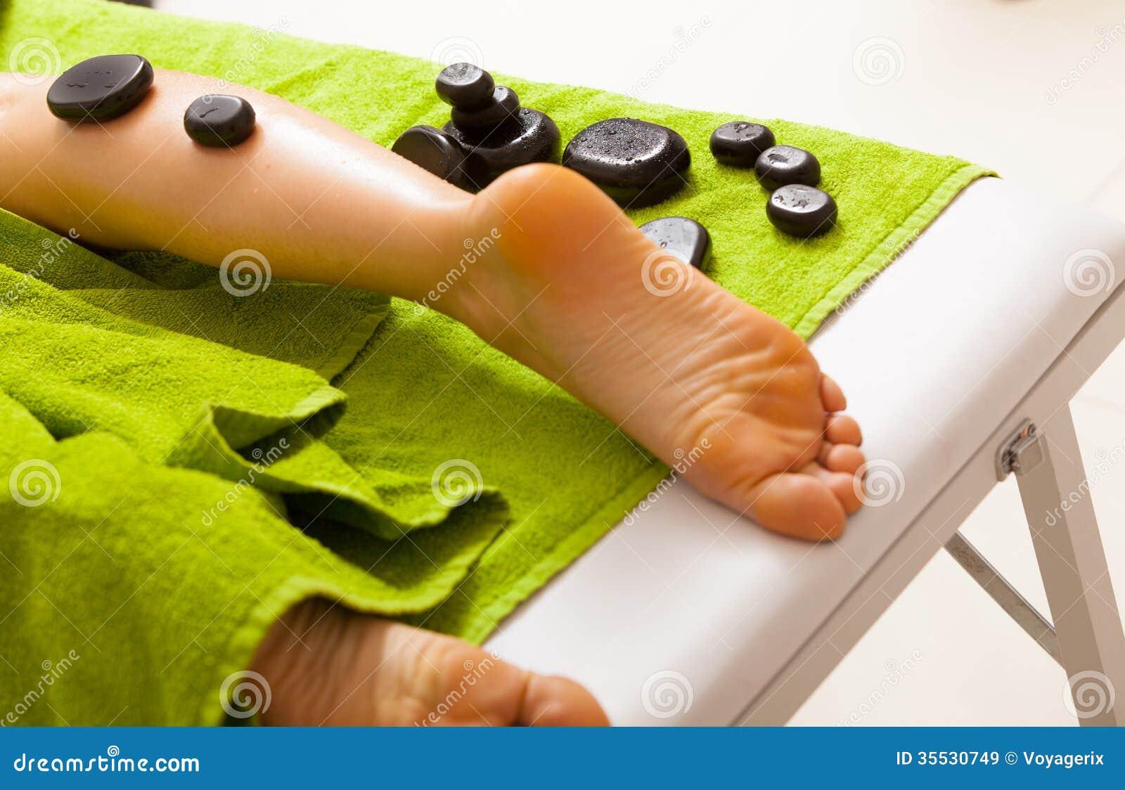 温泉沙龙。有女性的腿热的石按摩。Bodycare和放松。