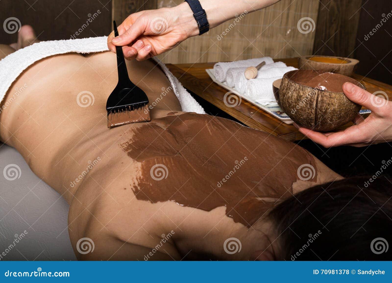 温泉沙龙的女孩,巧克力身体套治疗,皮肤回复 秀丽处理概念
