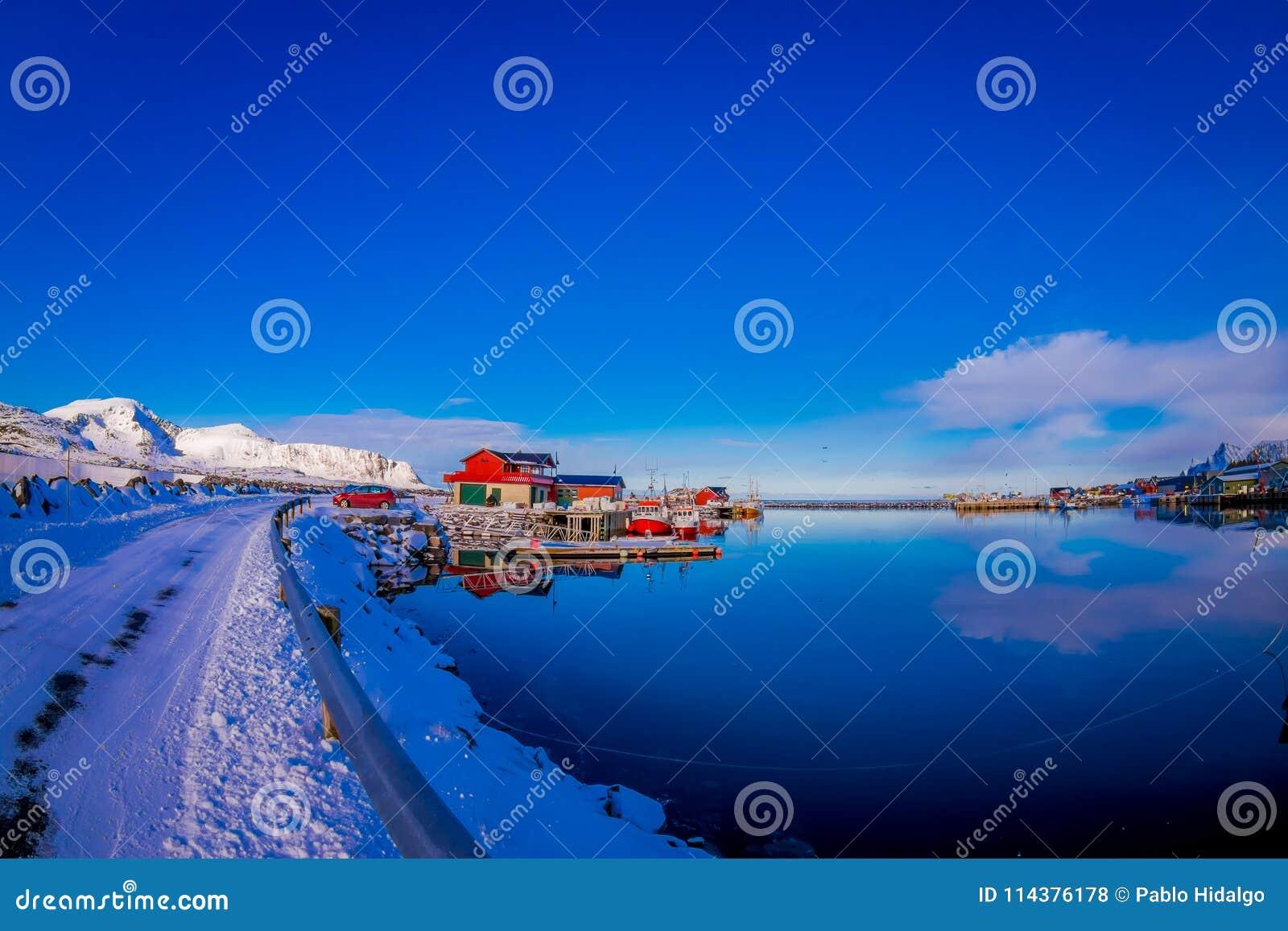 港口区域室外看法与钓鱼从路后边观看的木大厦的,盖用雪在Svolvaer