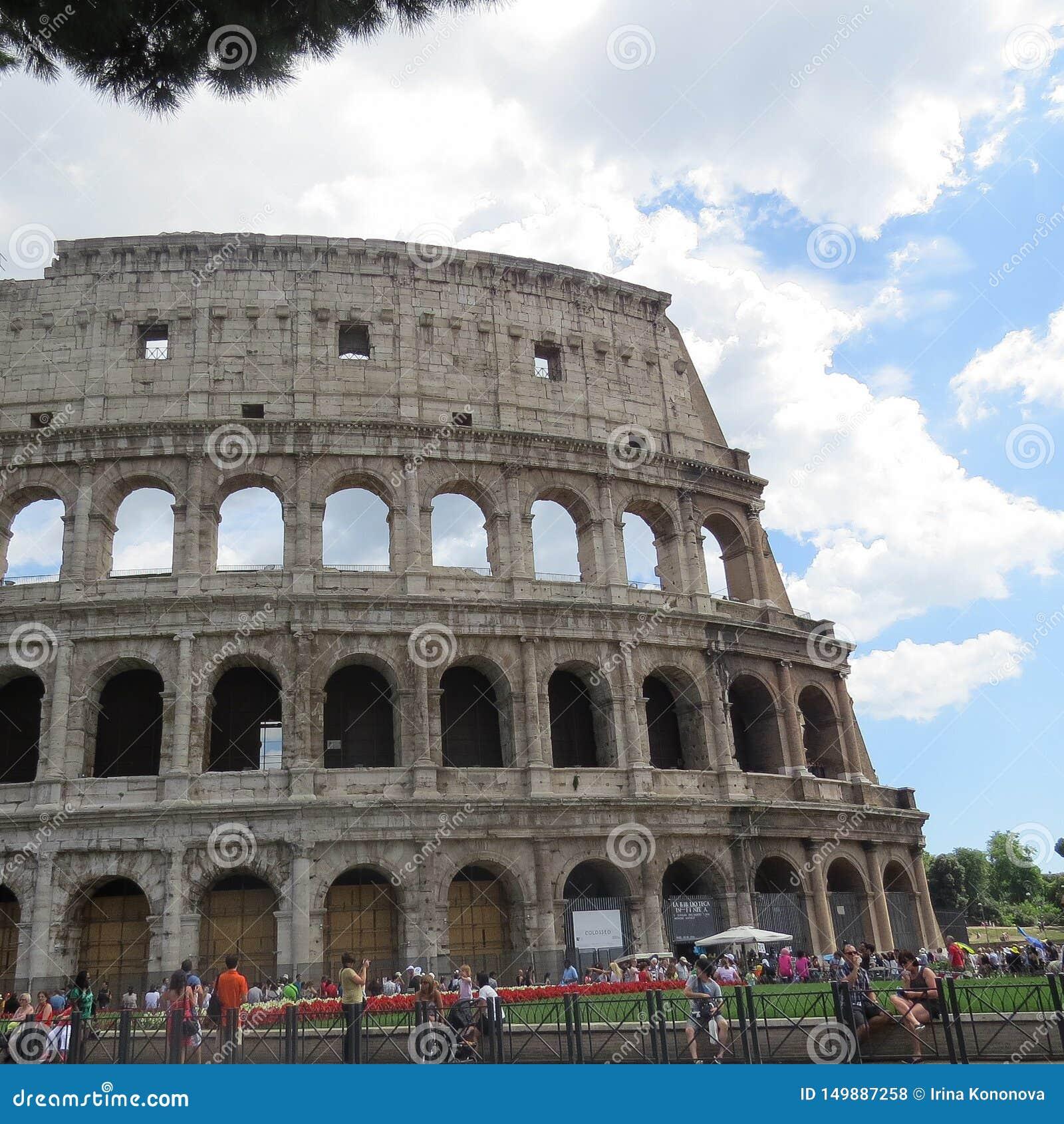 游人和罗马斗兽场的墙壁在反对蓝色多云天空的罗马