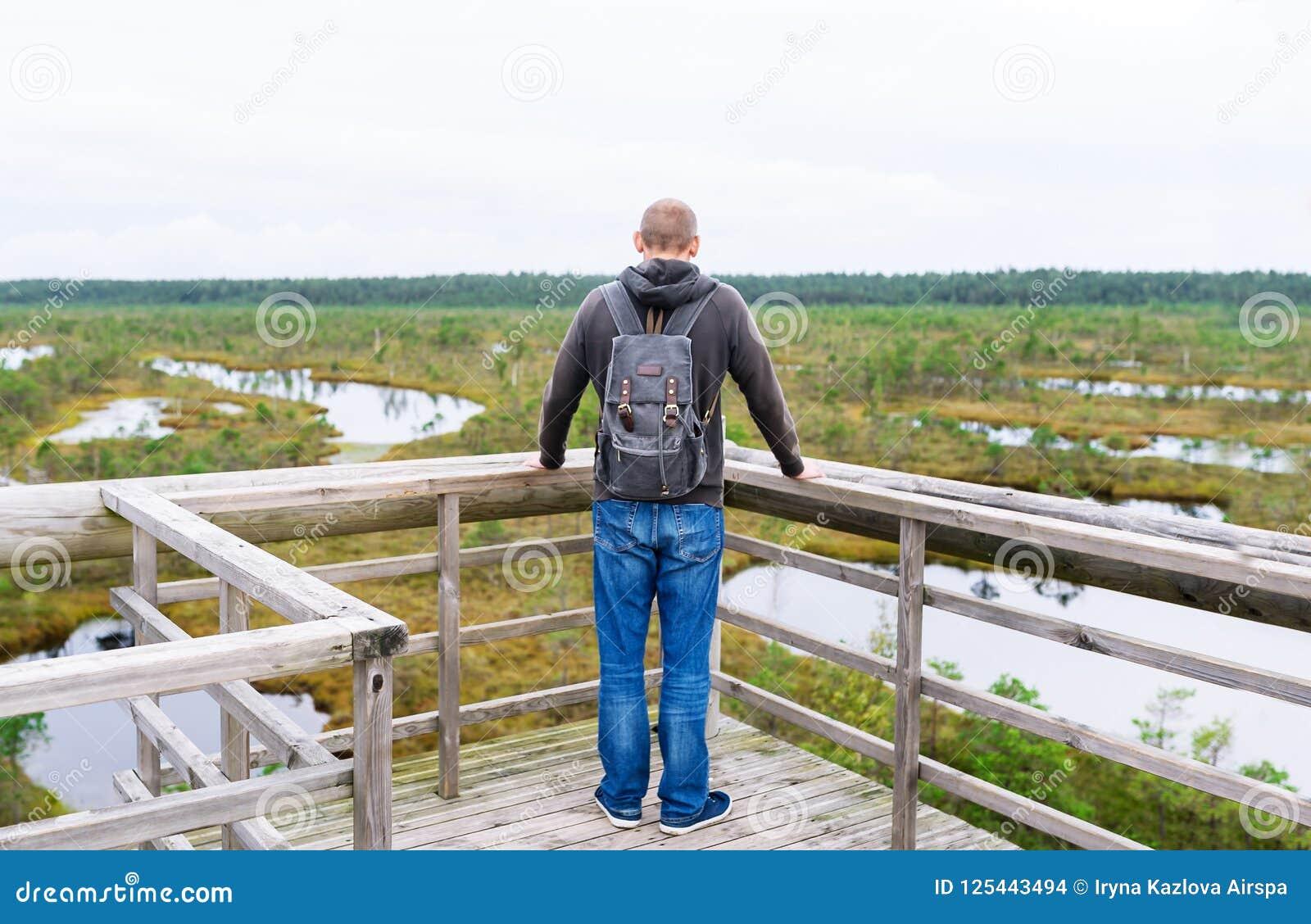 游人在有背包的桥梁停下来享受自然在夏日