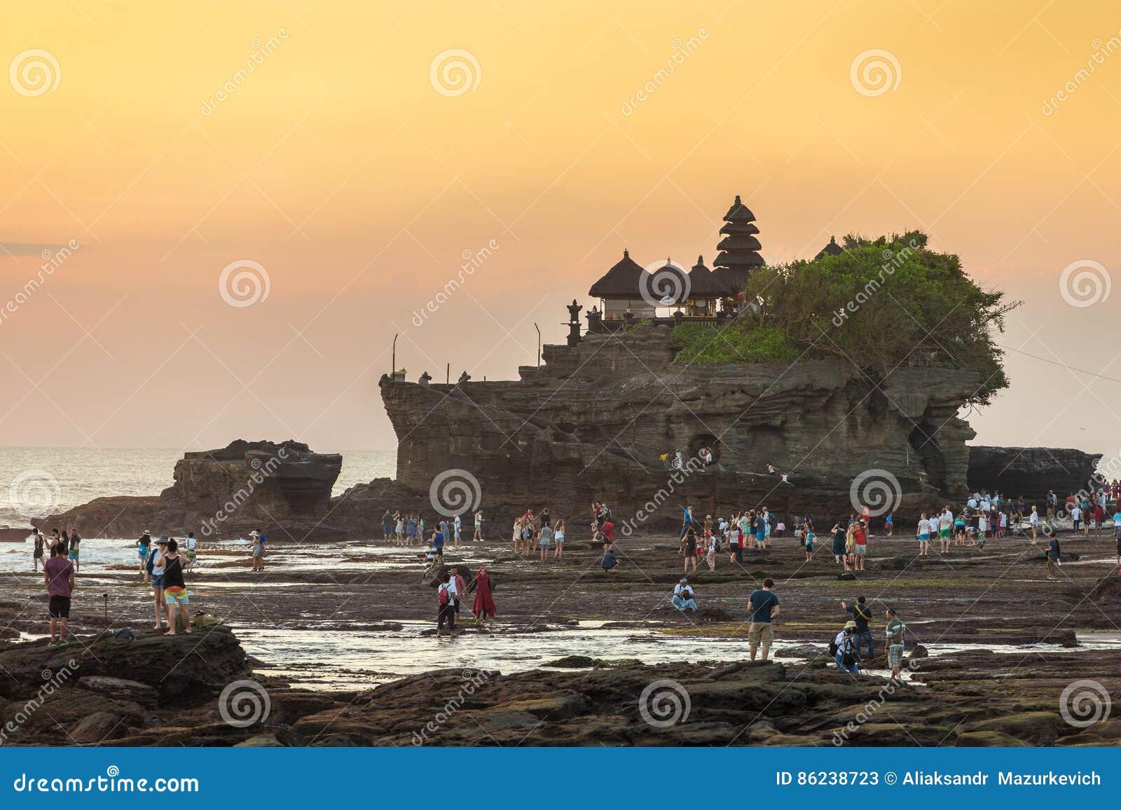 游人在Tanah全部寺庙附近走在日落期间在巴厘岛