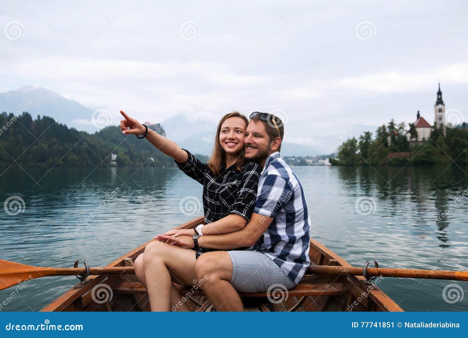 游人年轻夫妇木小船的在布莱德湖,斯洛文尼亚