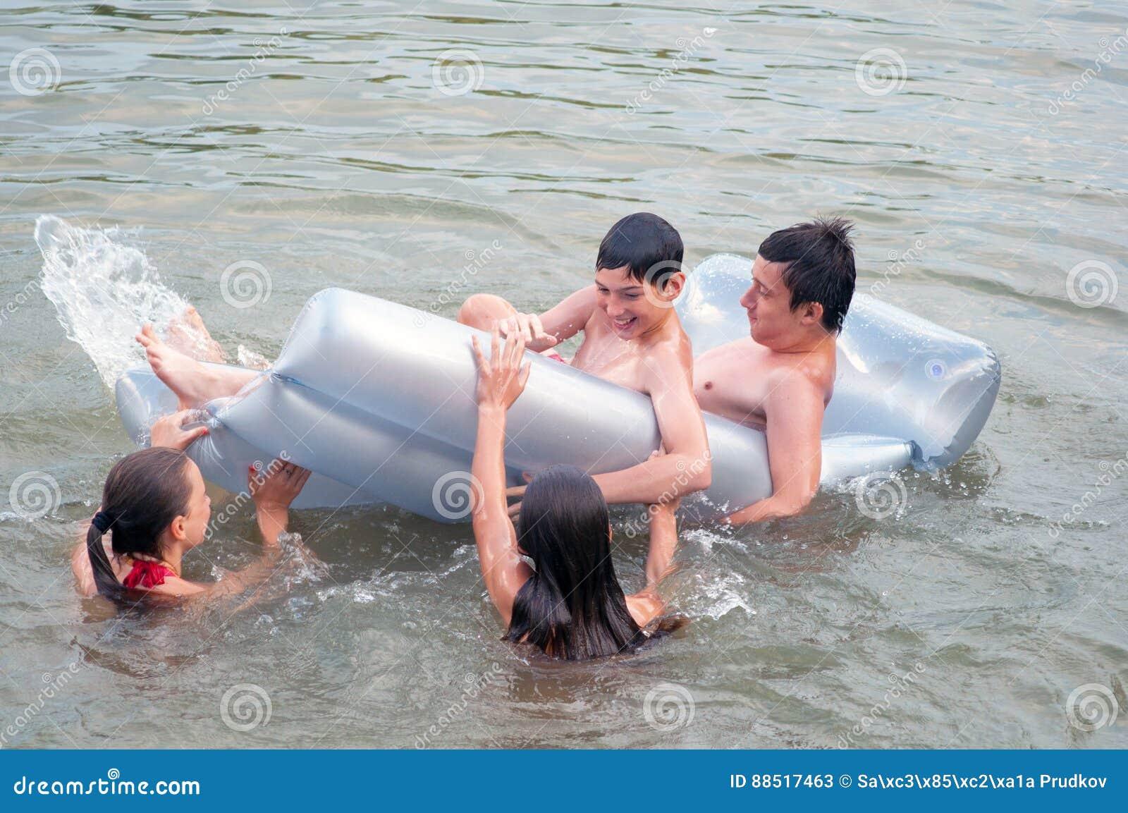 游泳和使用在河的十几岁的男孩和女孩在夏天