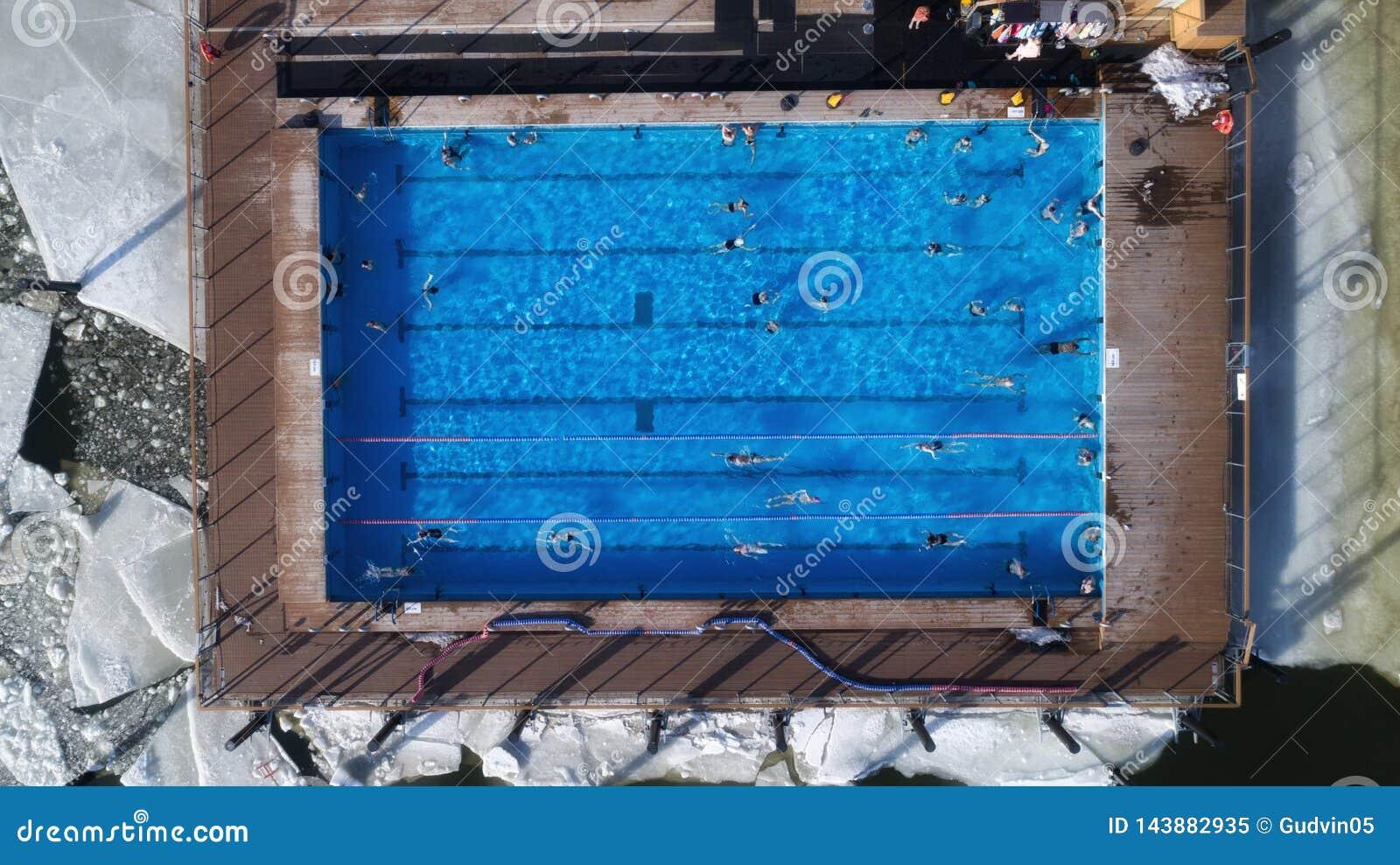 游泳在水池的人们在冬天顶视图角度