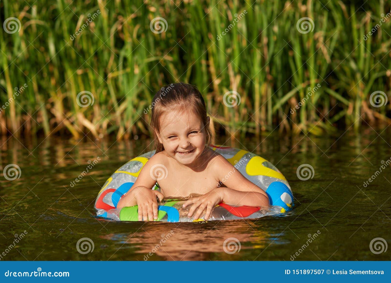 游泳在河的甜嬉戏的孩子画象用特别设备,去学会游泳,有宜人的脸面护理