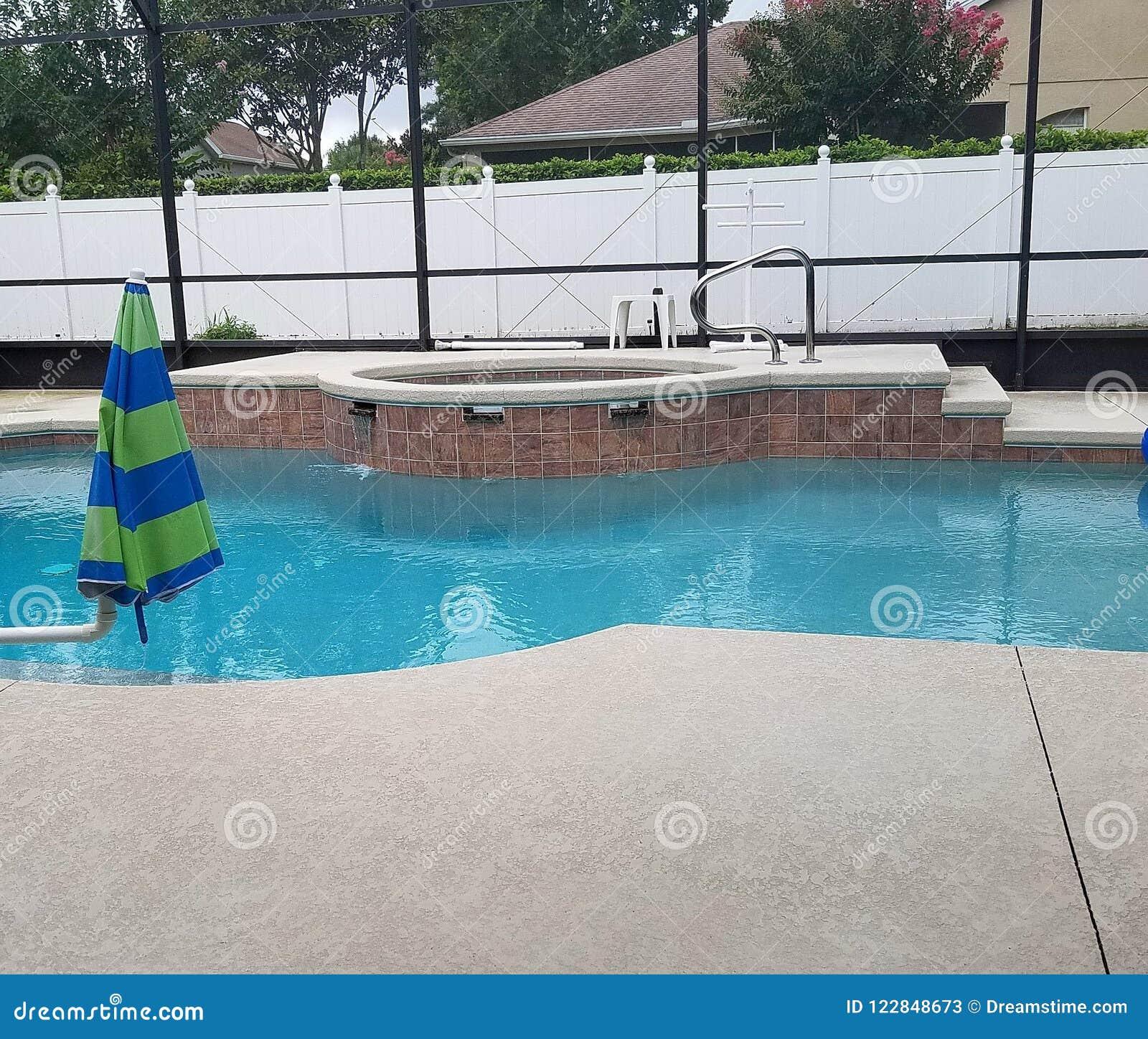 游泳池在有水池甲板和温泉极可意浴缸的屏幕封入物