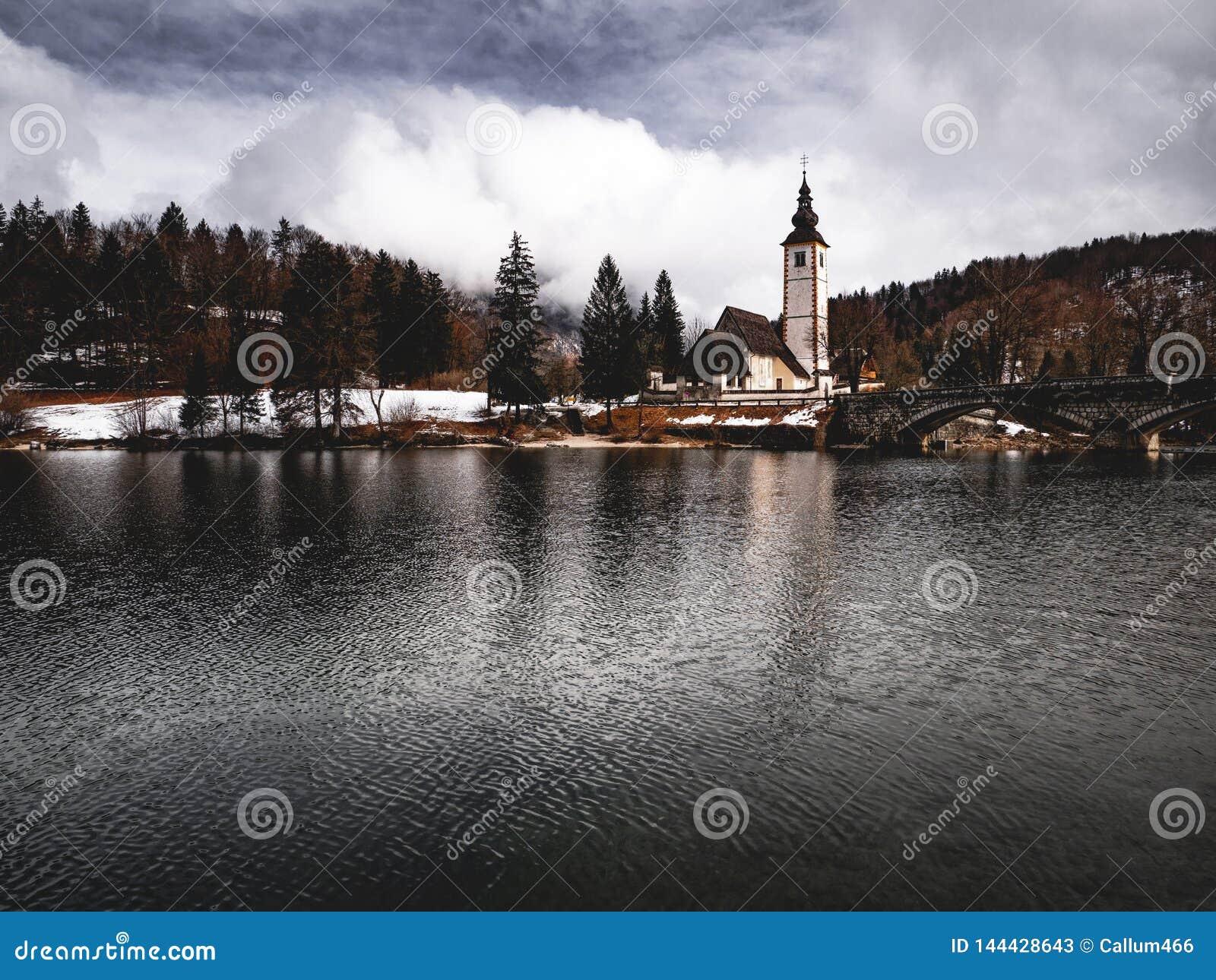 湖边教会有树木繁茂的背景