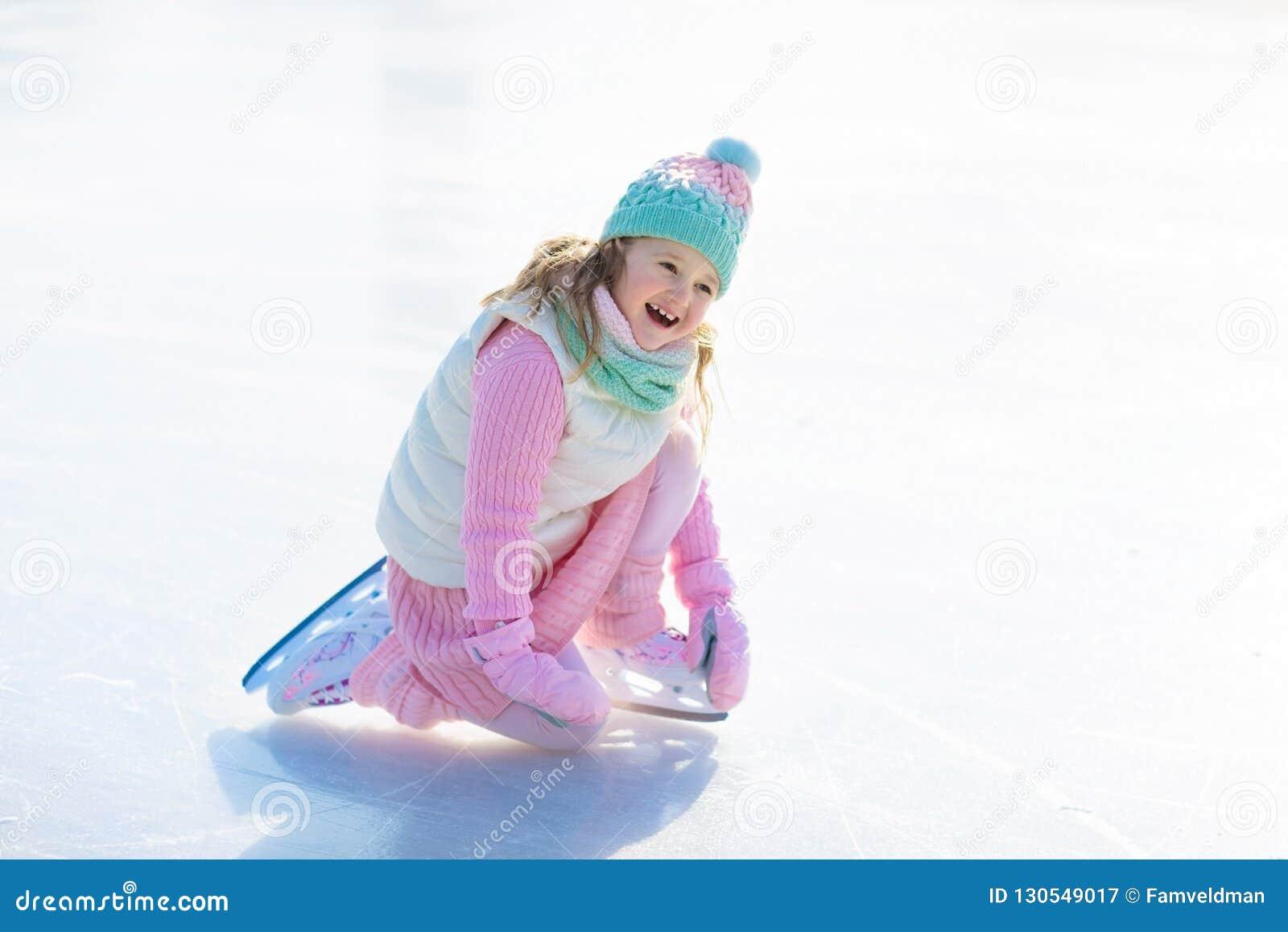 滑冰在天然冰的孩子 与冰鞋的孩子