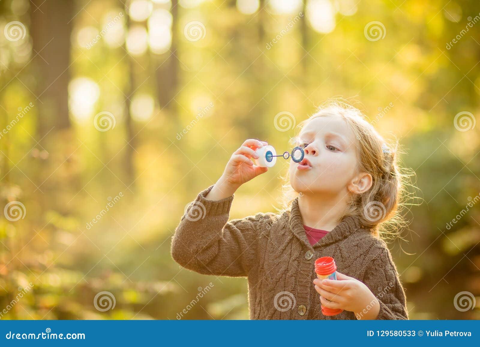 滑稽的可爱的小女孩吹的肥皂泡画象  黄色被编织的外套的逗人喜爱的白肤金发的蓝眼睛的女孩在