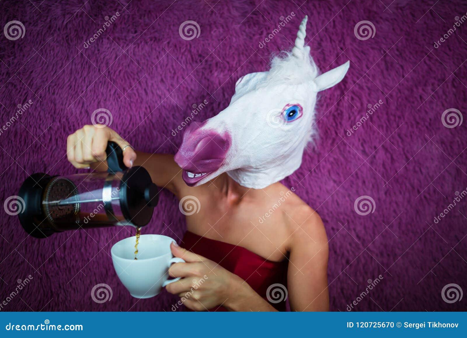 滑稽的女孩独角兽倒茶 可笑面具的怪异的少妇