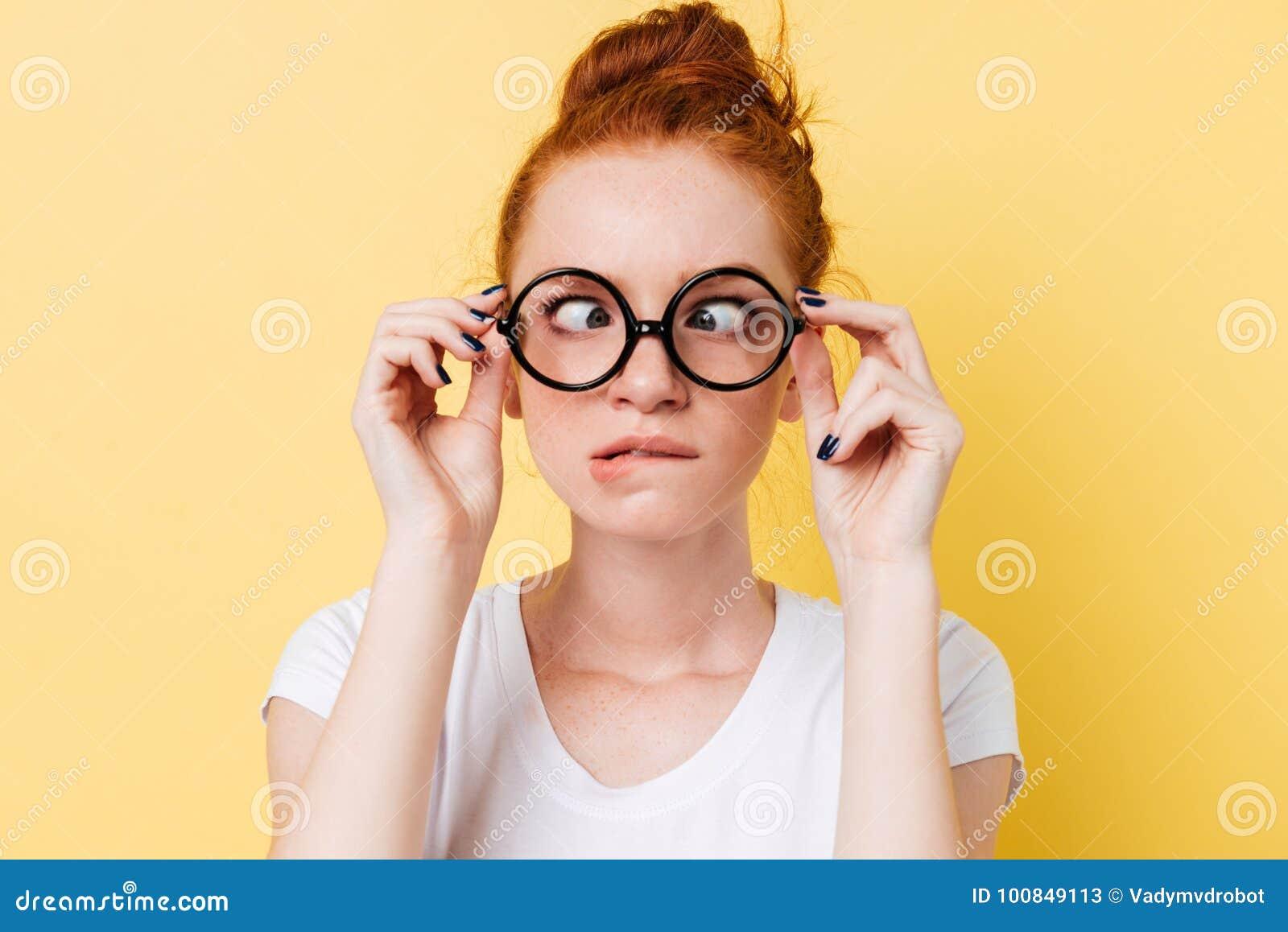 滑稽的姜妇女的特写镜头图片显示鬼脸的eyeglasess的