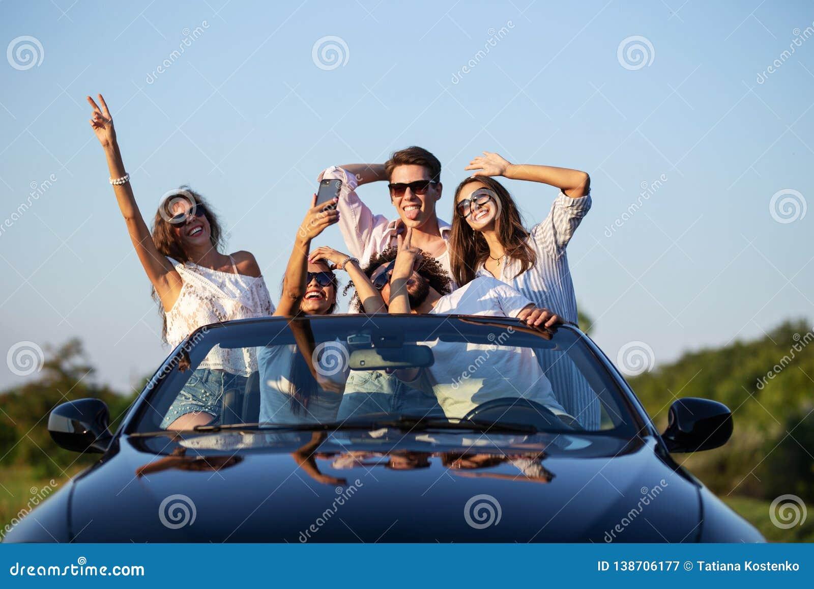 滑稽的少女和人太阳镜的在黑敞蓬车坐停滞他们的手和做的路