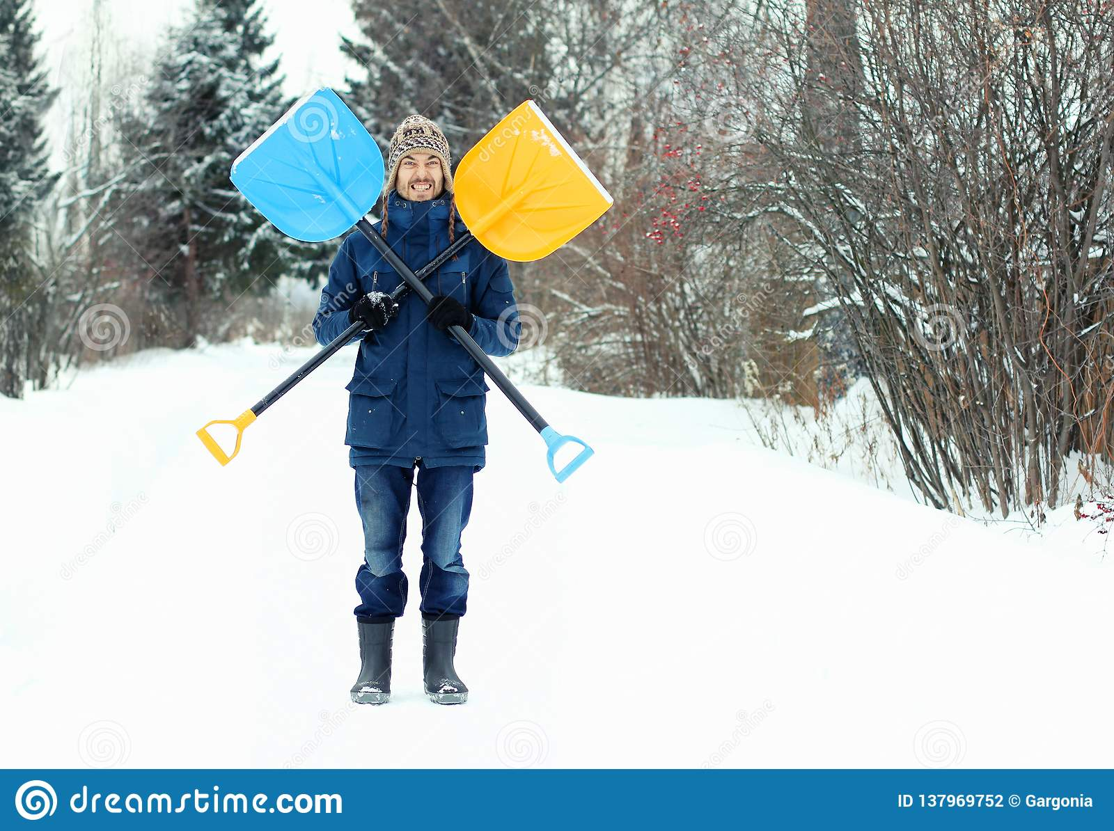 滑稽的年轻人拿着两把雪铁锹,形成海盗旗的标志 冬天季节性概念