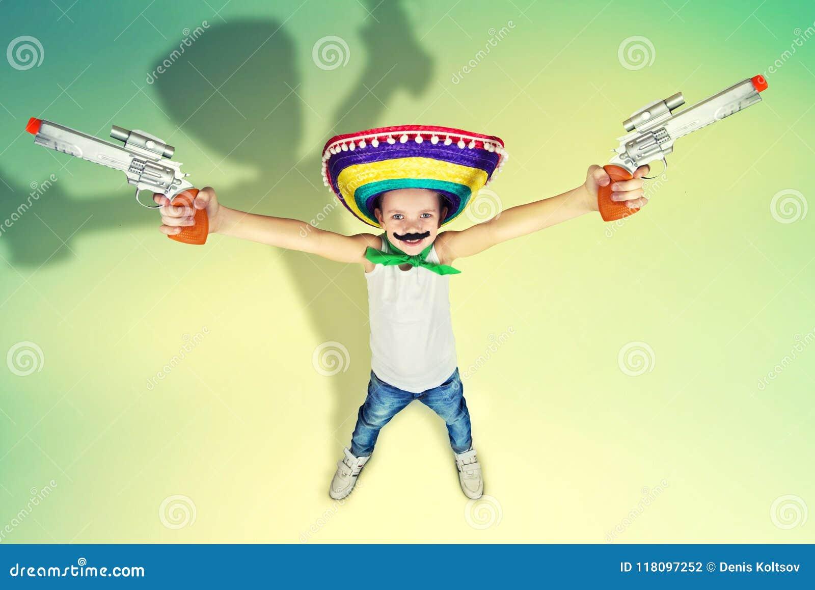 滑稽的男孩有一根假髭的和墨西哥阔边帽的使用与玩具手枪