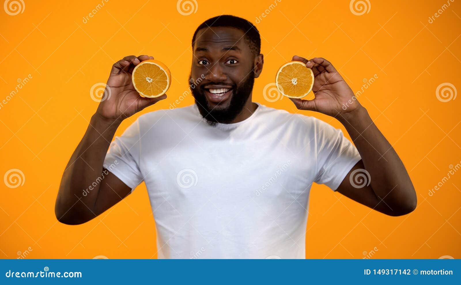 滑稽的美国黑人的人藏品一半桔子,健康素食营养