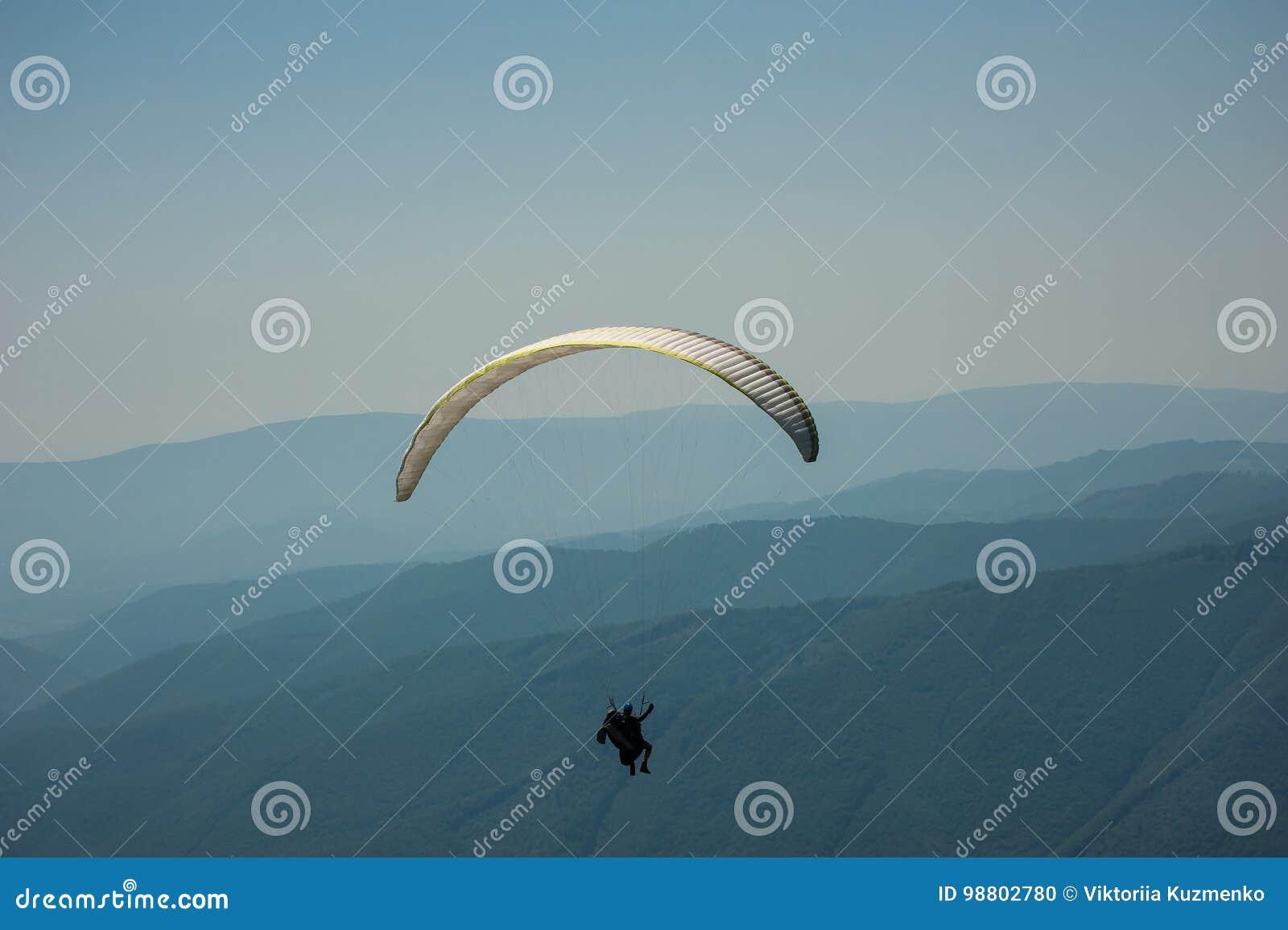 滑翔伞一前一后飞行在一个晴朗的总和的一个山谷