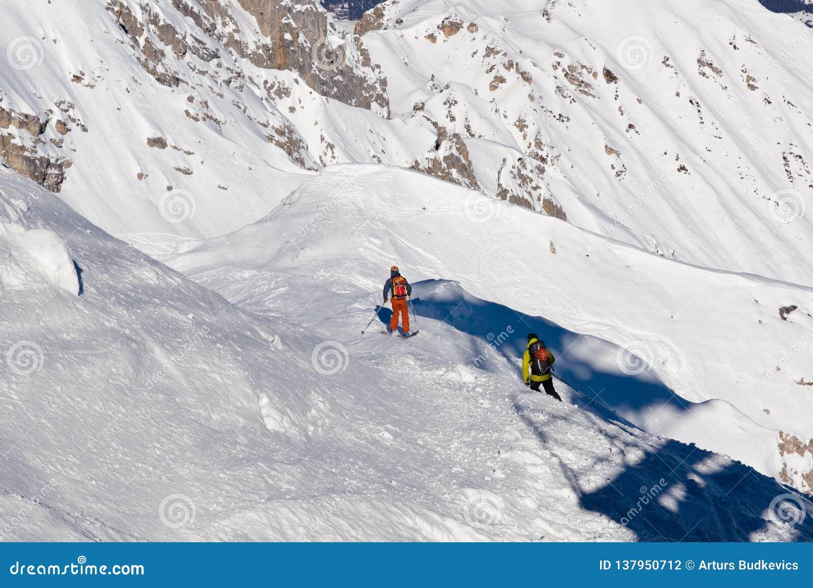 滑雪,滑雪者,在新鲜的粉末雪-有滑雪攀登的人的不劳而获在上面