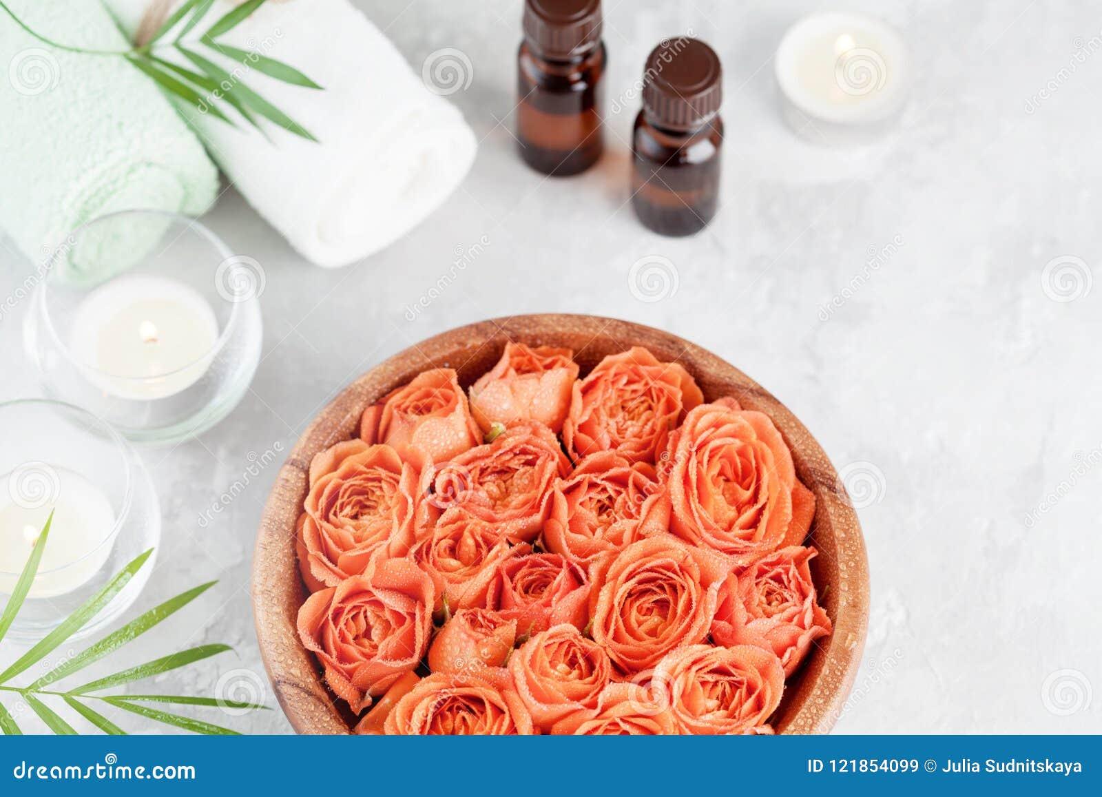 滚保龄球与新鲜弄湿温泉、健康和芳香疗法的玫瑰色和精油瓶