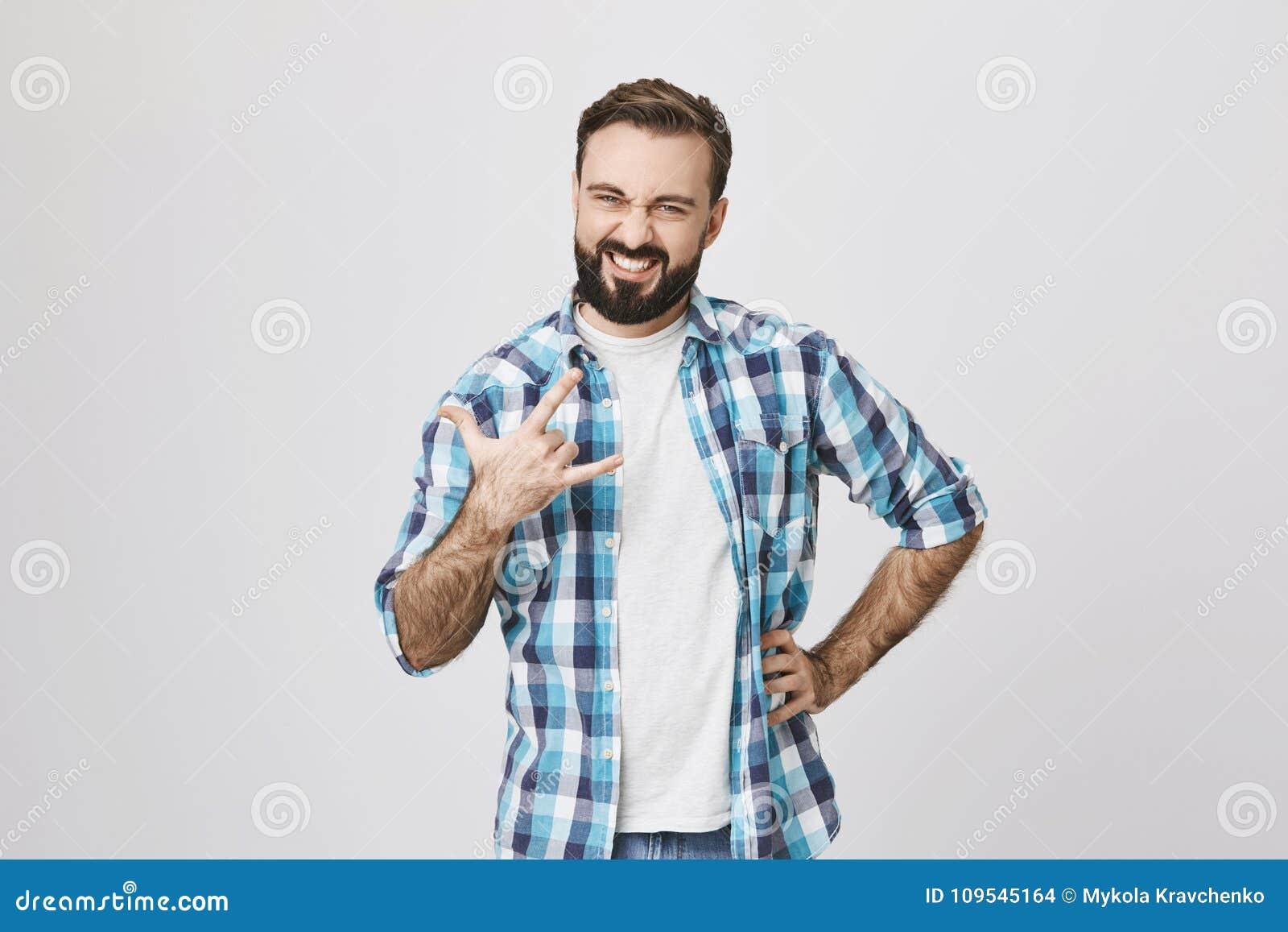 满意和确信的看起来的有胡子的人画象,握在腰部的一只手和做岩石姿态用别的