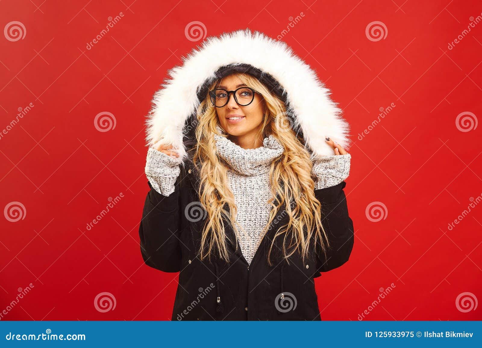 满意的妇女画象,穿有敞篷的一件温暖的冬天夹克,有快乐的表示,感到温暖和舒适