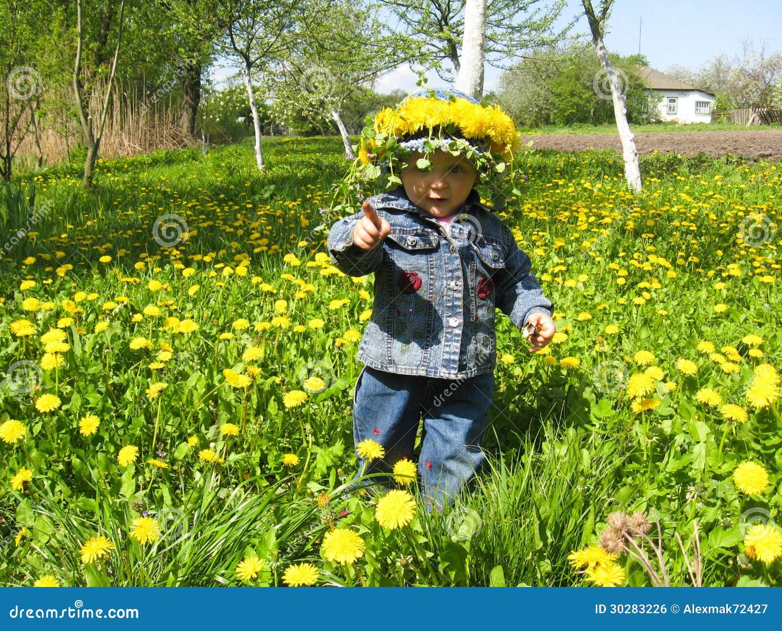 漂亮的孩子用蒲公英在春天