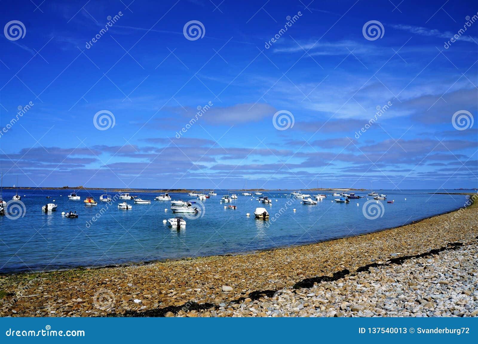 漂浮在水中的小船在附近小卵石在布里坦尼靠岸