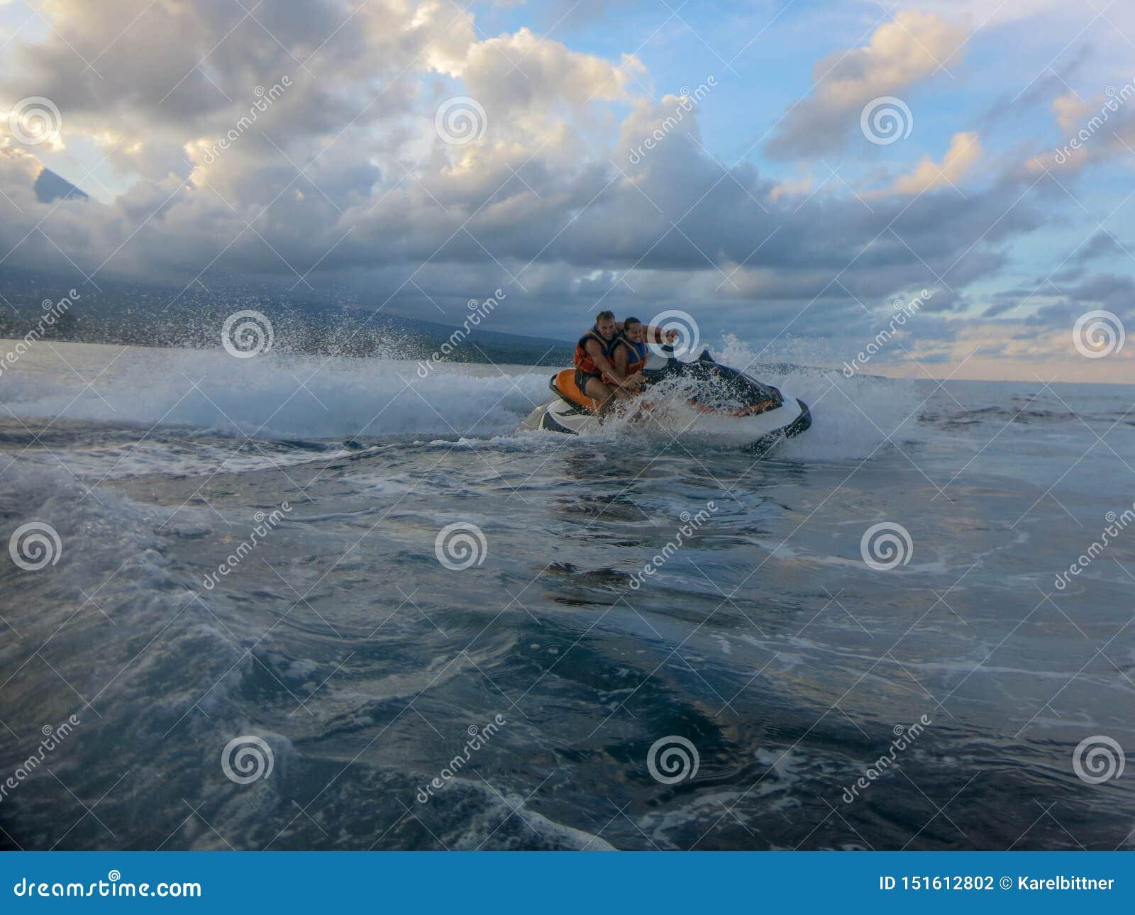 漂移横跨海表面的年轻人和妇女 喷气机滑雪的人们获得乐趣在海洋 在行动的司机在飞溅水期间