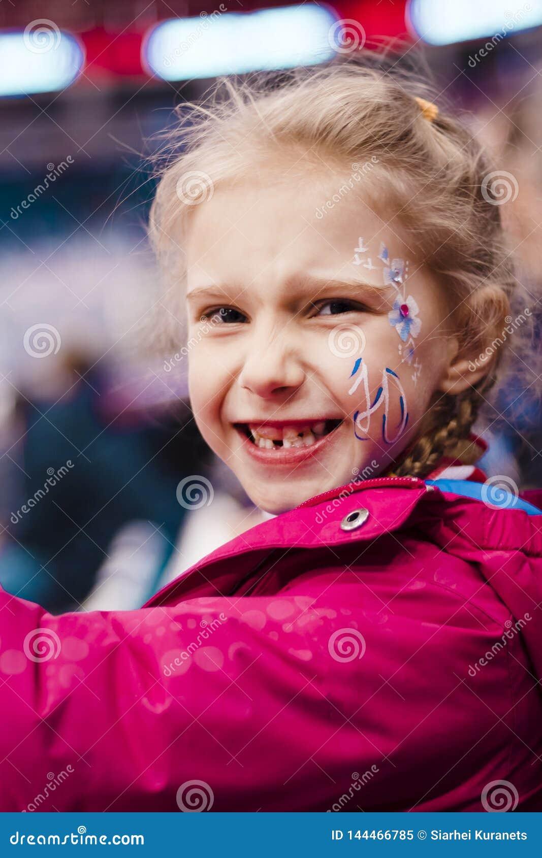 演出的照片 指挥台的女孩金发碧眼的女人 有在面颊的题字 她是高兴的队赢得 ?