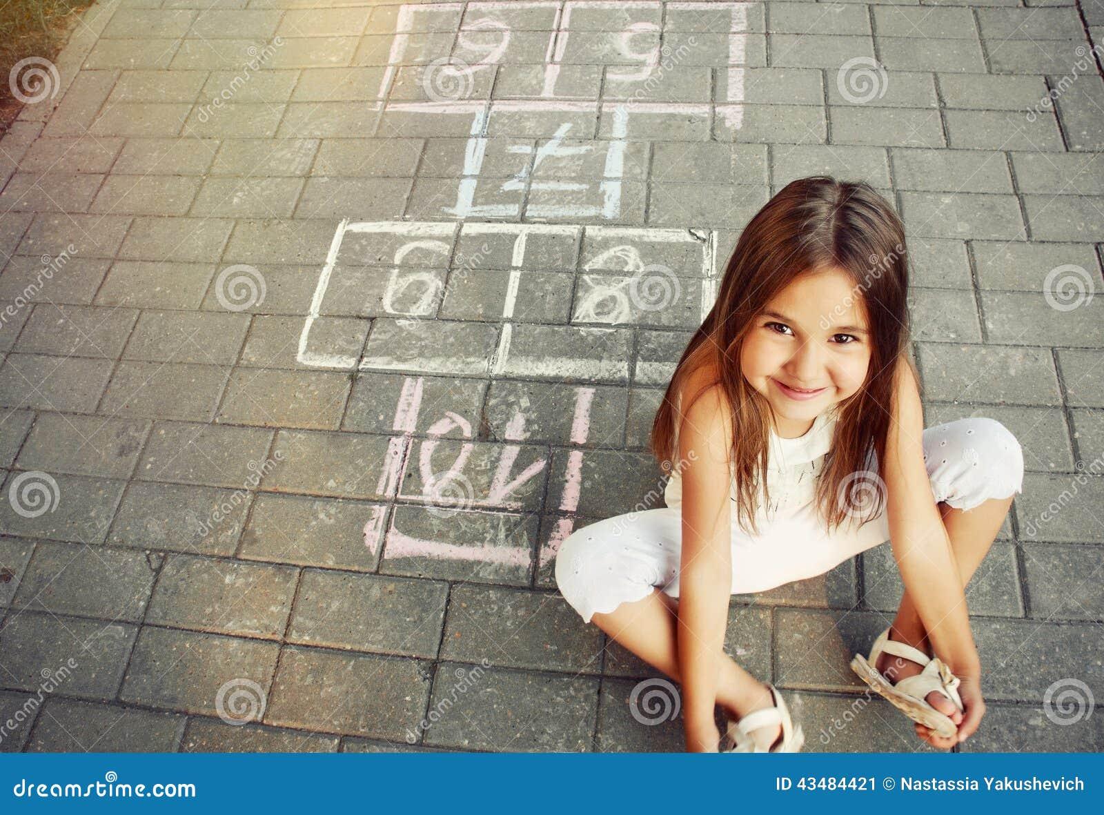 演奏在操场的美丽的快乐的小女孩跳房子
