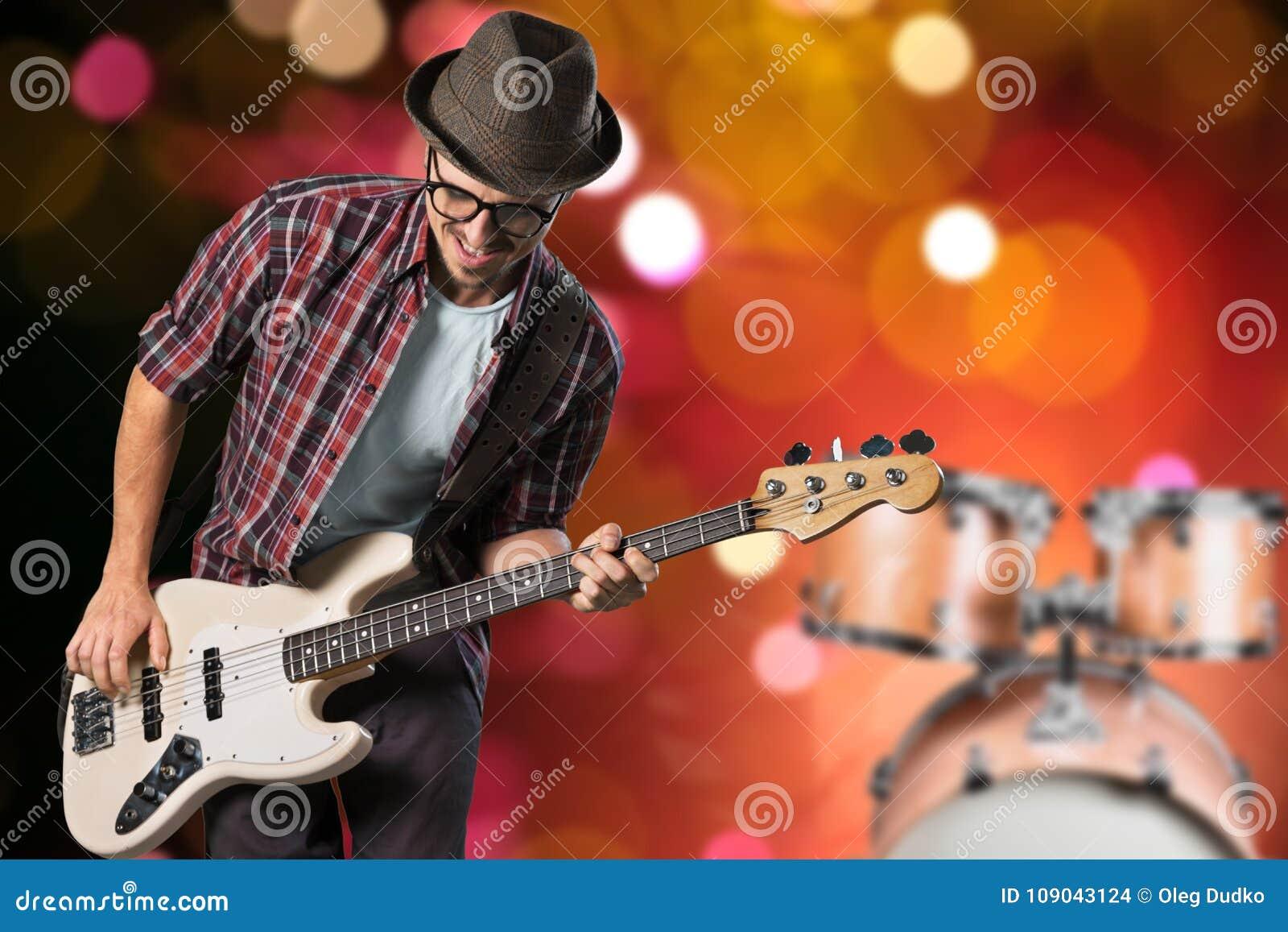 演奏在被弄脏的背景的男性吉他弹奏者音乐