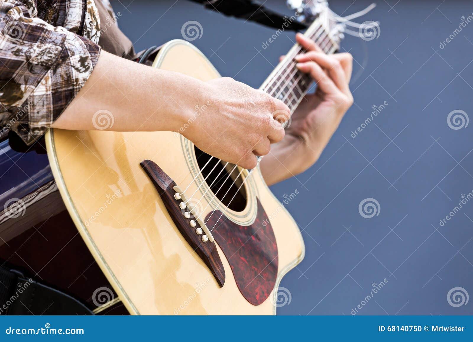 演奏声学吉他特写镜头的妇女的手