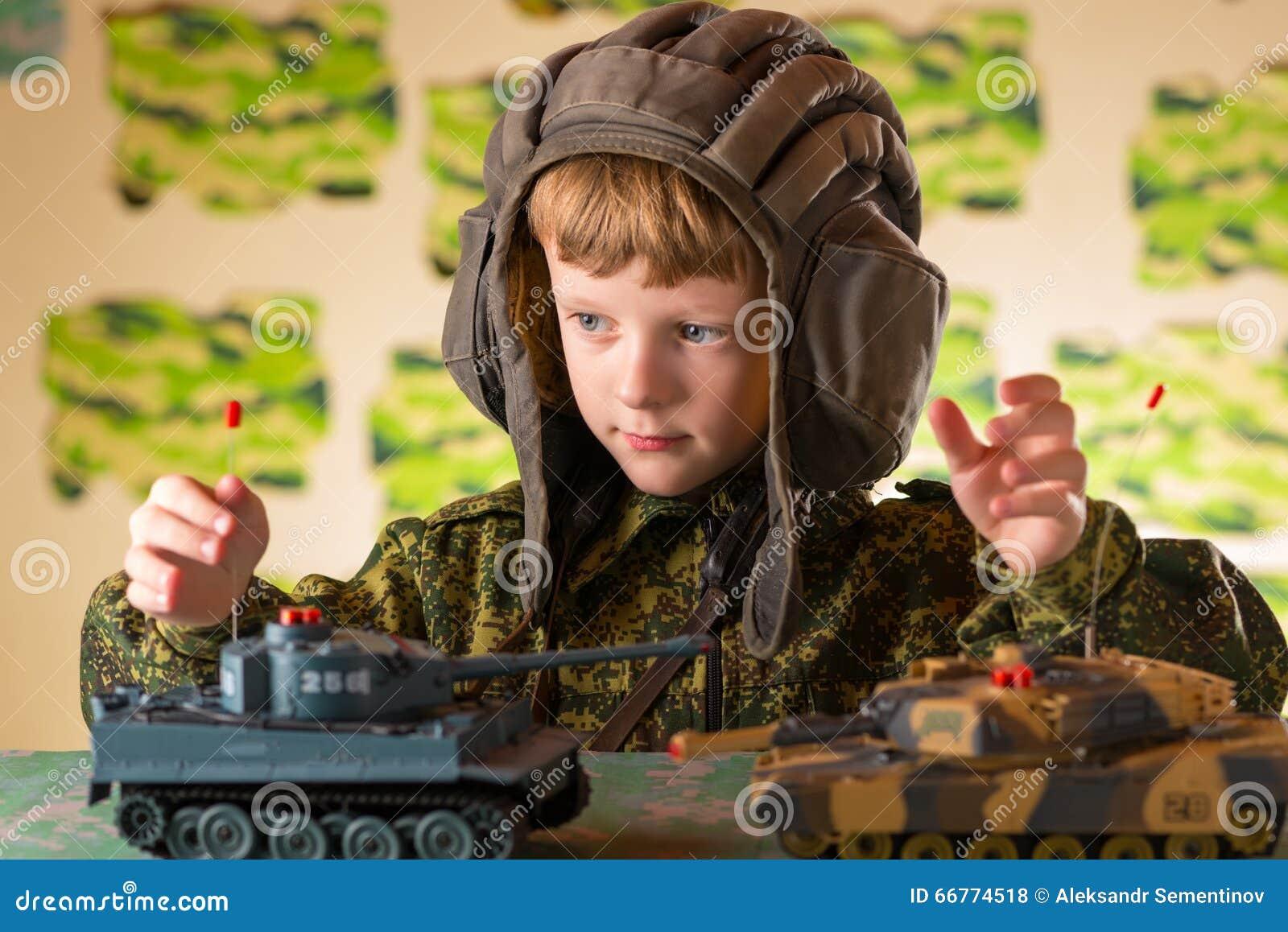 演奏玩具军事坦克的男孩