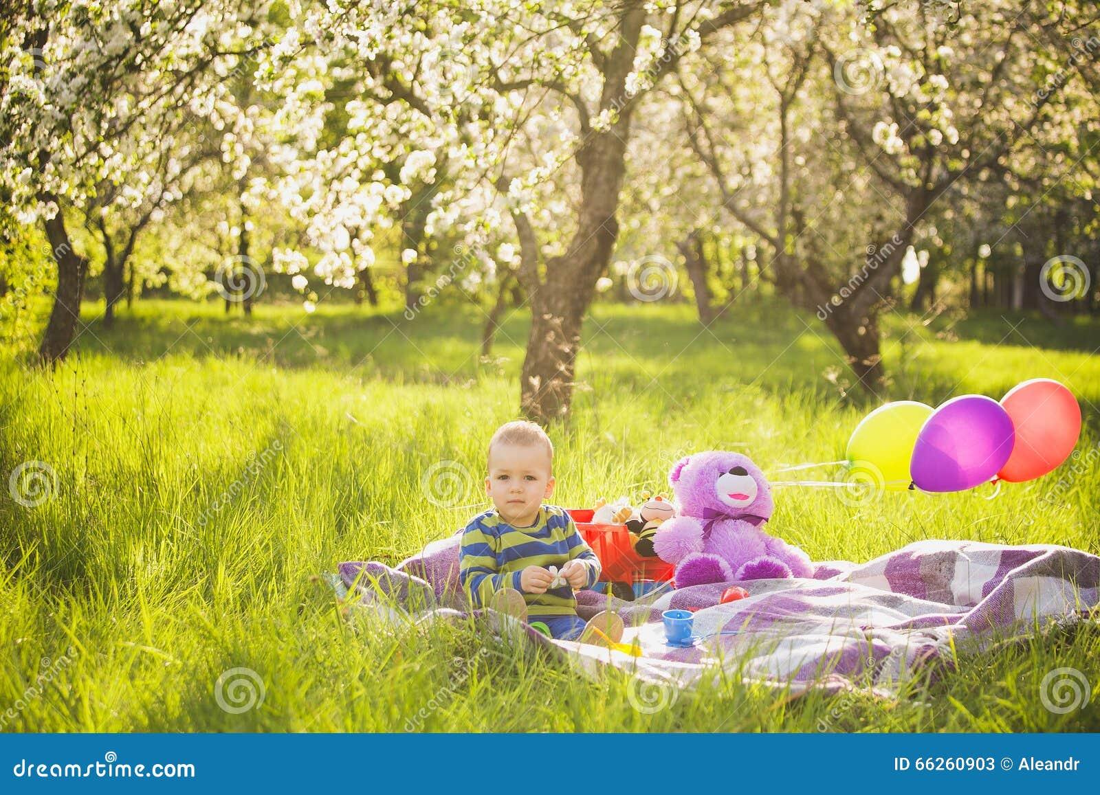 演奏玩具的小男婴坐美国钞票草外面
