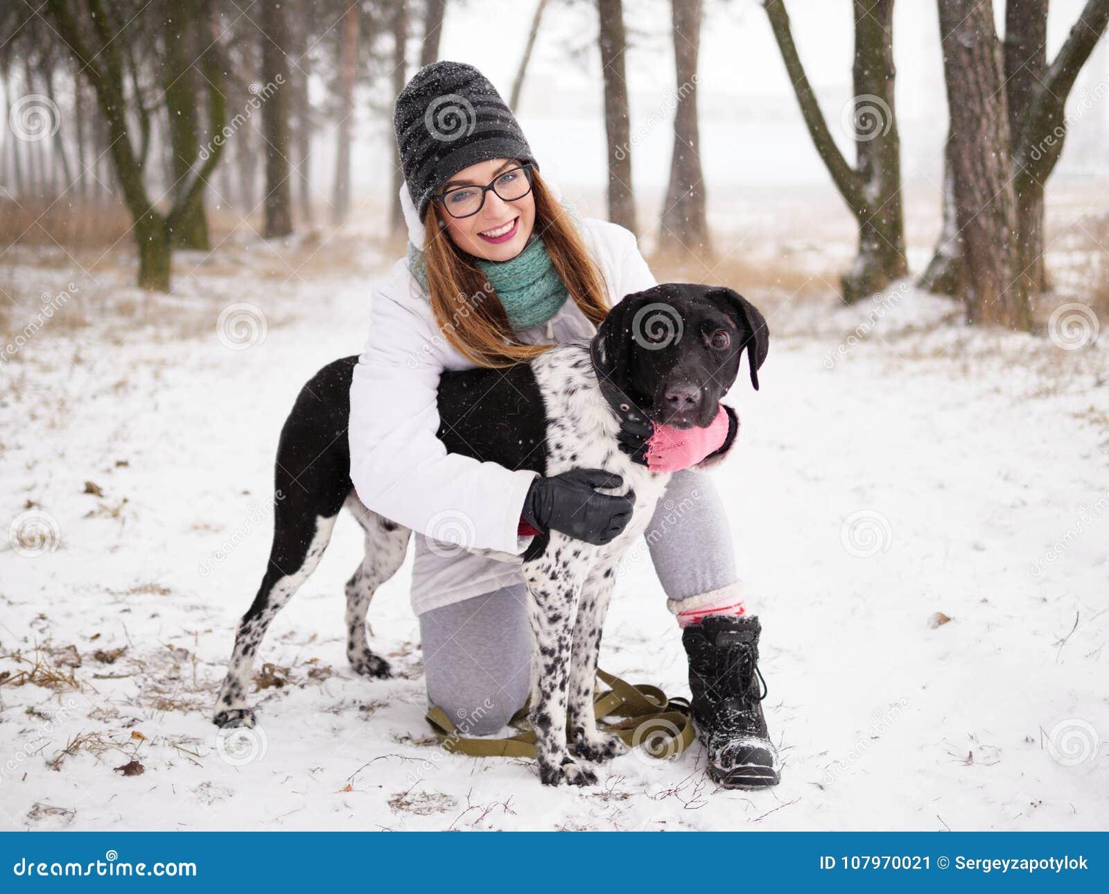 演奏雪冬天的少妇户外拥抱逗人喜爱的被采取的瞎的安装员狗 仁慈和人类概念