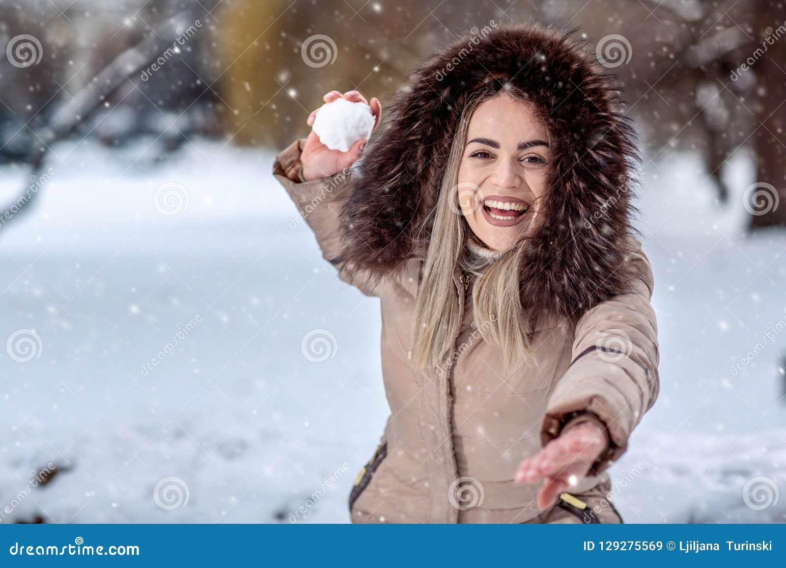 演奏雪球战斗的愉快的妇女在雪天 冬天conce