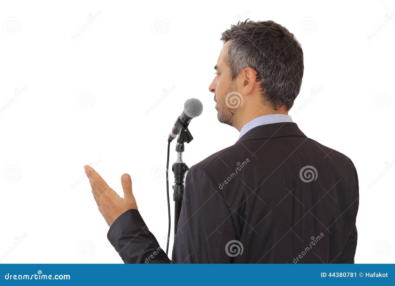 演讲人的背面图讲话在话筒