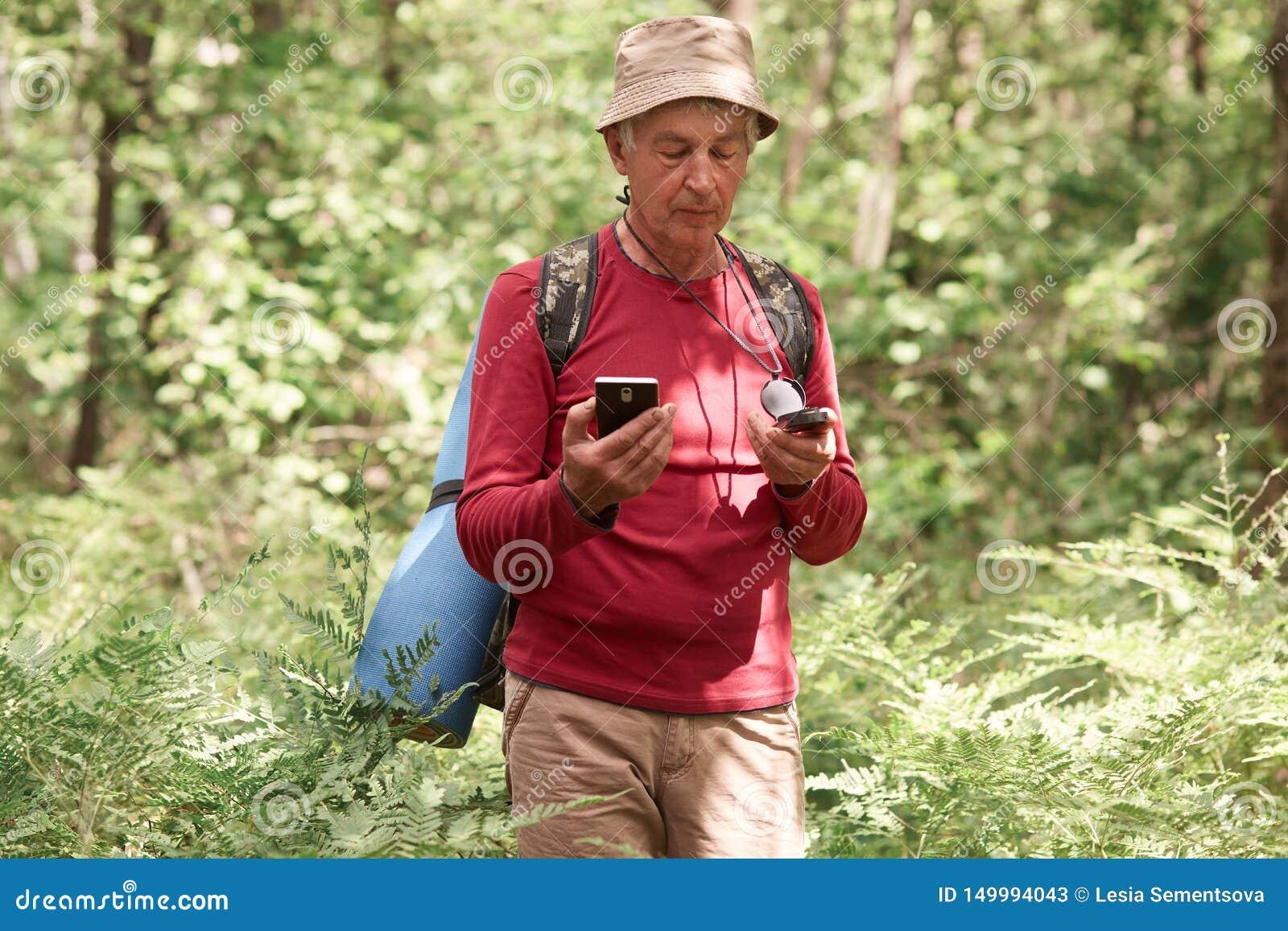 漫步在森林里的严肃的热心人,拿着指南针和智能手机在他的手上,选择他的旅行路线,是